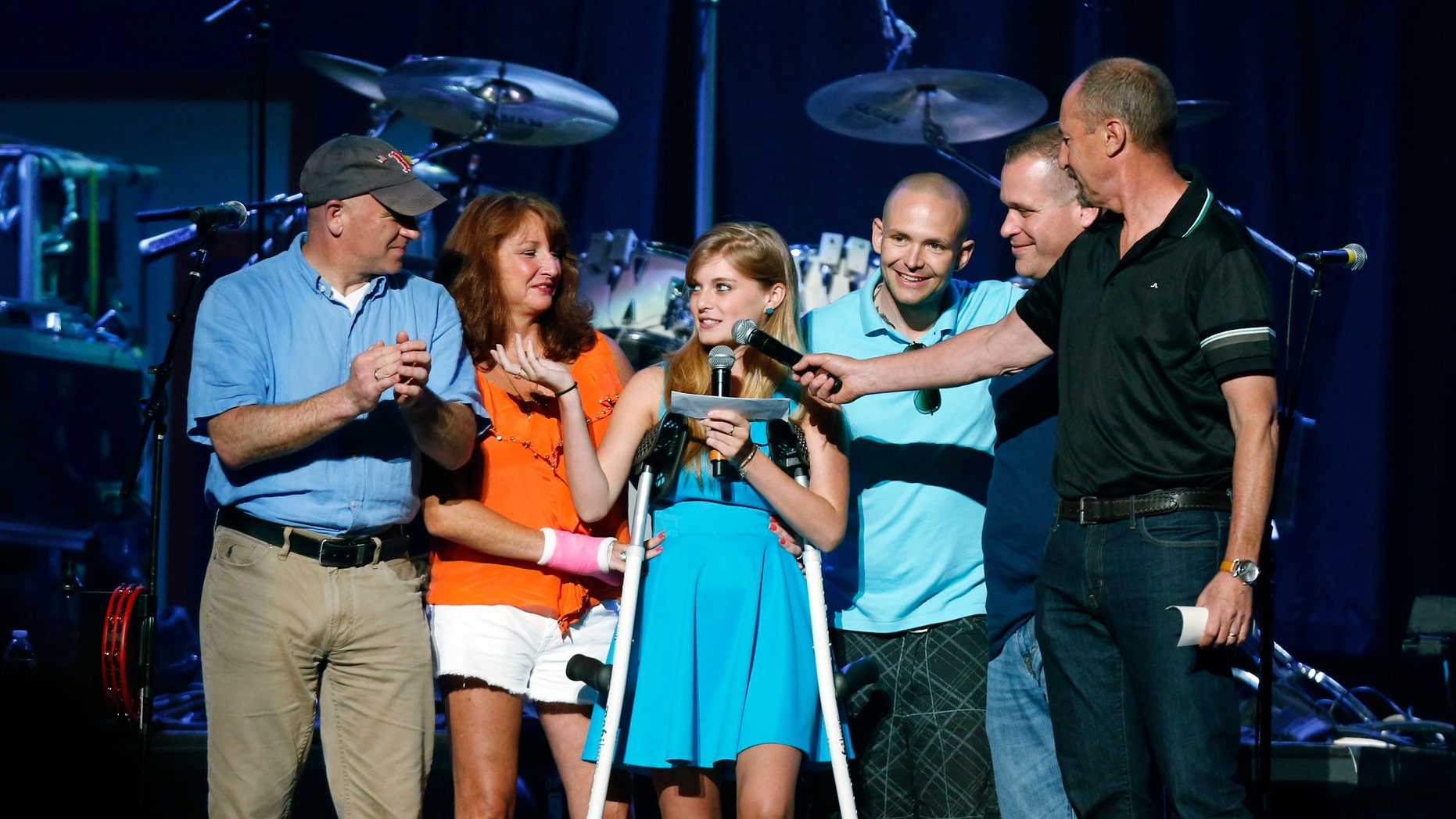 FILE - In this May 30, 2013 file photo, Boston Marathon bombing survivor Victoria McGrath, center, thanks people who helped her after she was injured in the bombing, during the Boston Strong Concert: An Evening of Support and Celebration at the TD Garden in Boston. A Northeastern University spokesman said Monday, March 7, 2016, that McGrath, originally from Westport, Conn., and another student were killed in a car accident in Dubai over the weekend while on a personal trip. (Photo by Bizuayehu Tesfaye/Invision/AP, File)