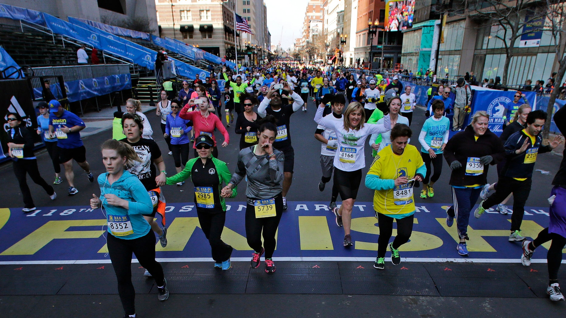 At the midpoint of the 5K race, runners cross the finish line of the Boston Marathon, Saturday, April 19, 2014, in Boston.