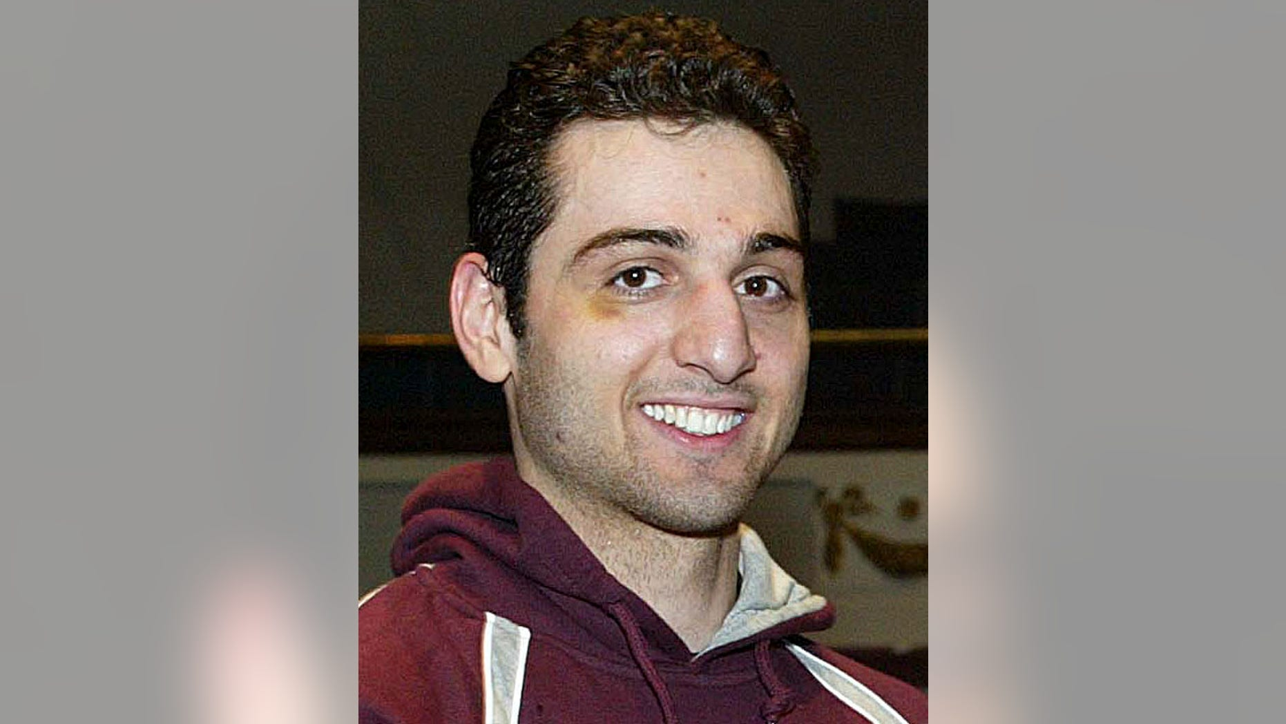 In this Feb. 17, 2010, photo, Tamerlan Tsarnaev, smiles after accepting the trophy for winning the 2010 New England Golden Gloves Championship from Dr. Joseph Downes, right, in Lowell, Mass.