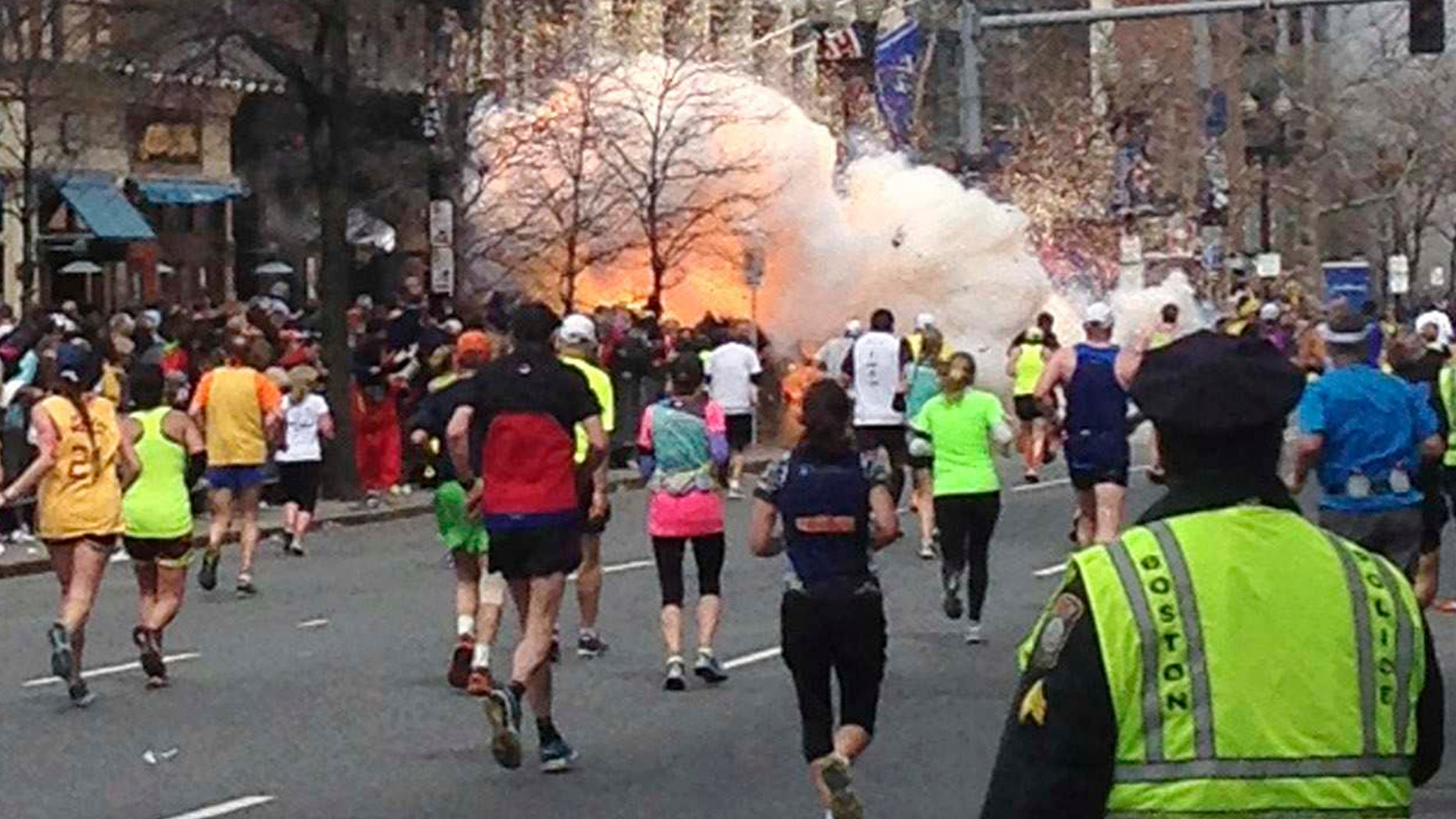 Runners continue to run towards the finish line of the Boston Marathon as an explosion erupts near the finish line of the race. (REUTERS/Dan Lampariello)
