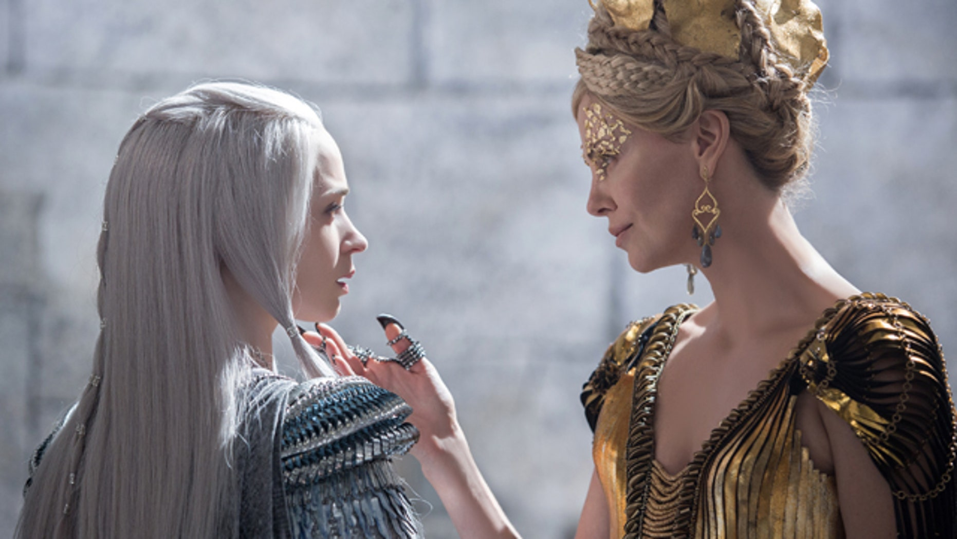 In this image released by Universal Pictures, Emily Blunt, left and Charlize Theron appear in a scene from 'Huntsman: Winter's War.' (Giles Keyte/Universal Pictures via AP)