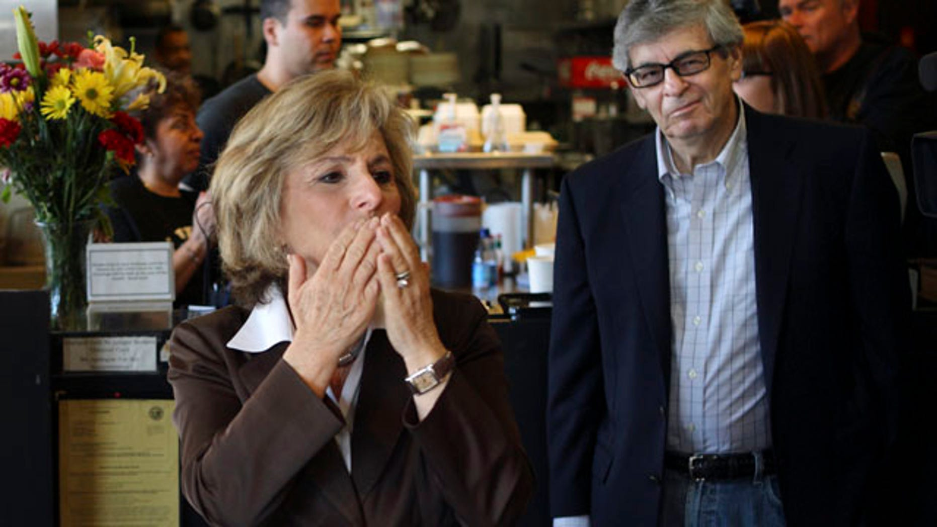 Sen. Barbara Boxer, accompanied by her husband Stewart, right, stops into the Oakland Grill, a favorite eatery, to thank supporters on this Election Day