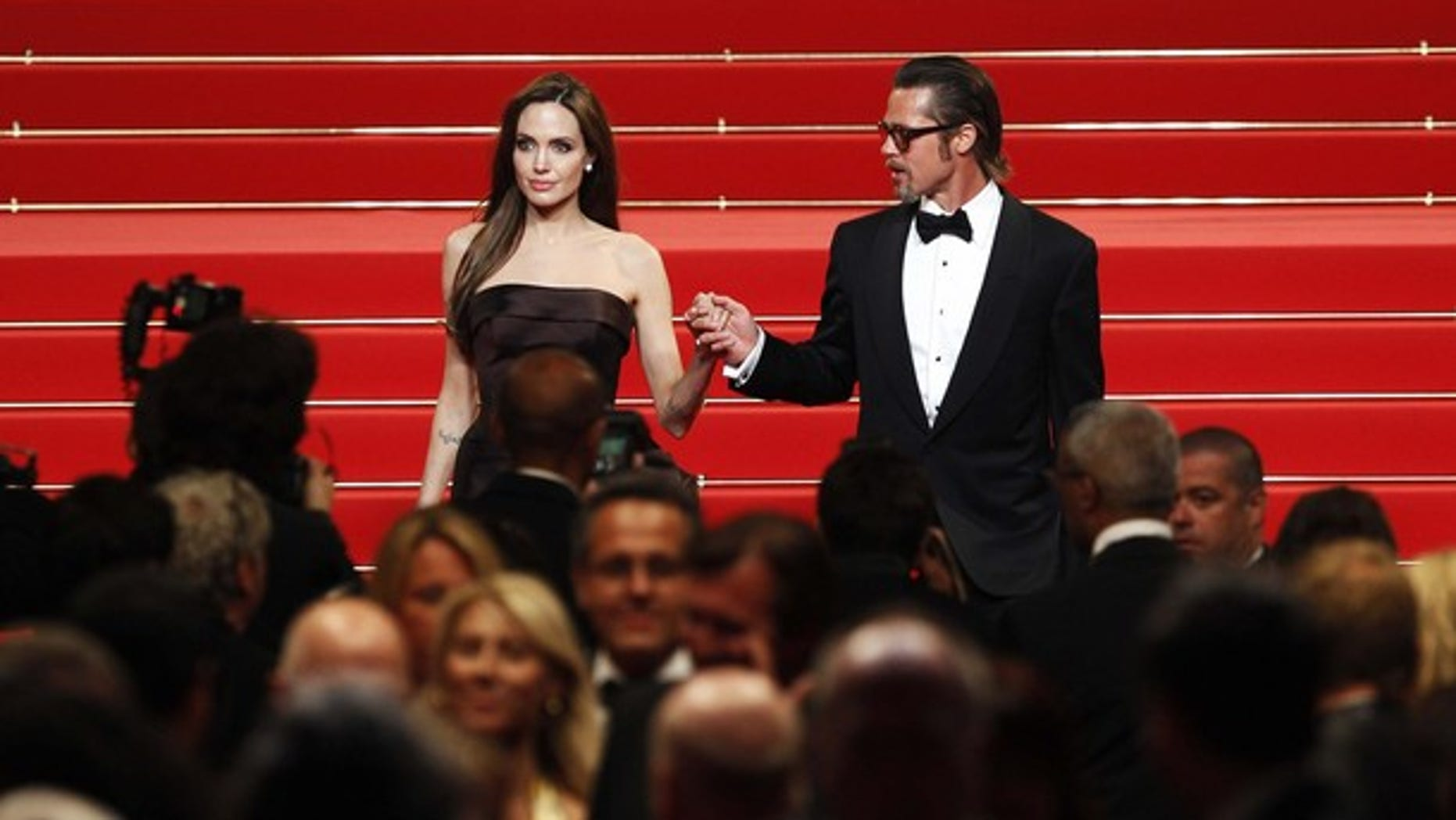 """May 16: Brad Pitt (R) and actress Angelina Jolie leave the festival palace after the screening of the film """"The Tree of Life"""". (Reuters)"""