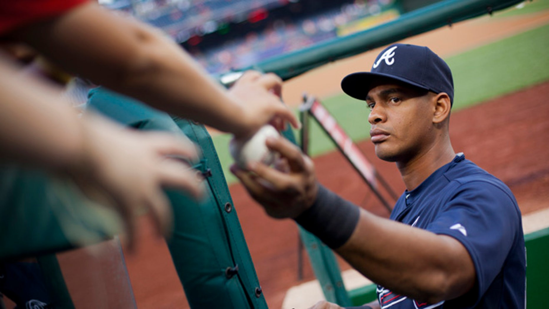 In this photo taken Sept. 3, 2015, Atlanta Braves Hector Olivera returns a ball as he signs autographs prior to start of a baseball game against the Washington Nationals, at Nationals Park in Washington. Police have arrested Olivera after a woman accused him of assault at a hotel outside in Arlington, Va. (AP Photo/Pablo Martinez Monsivais)