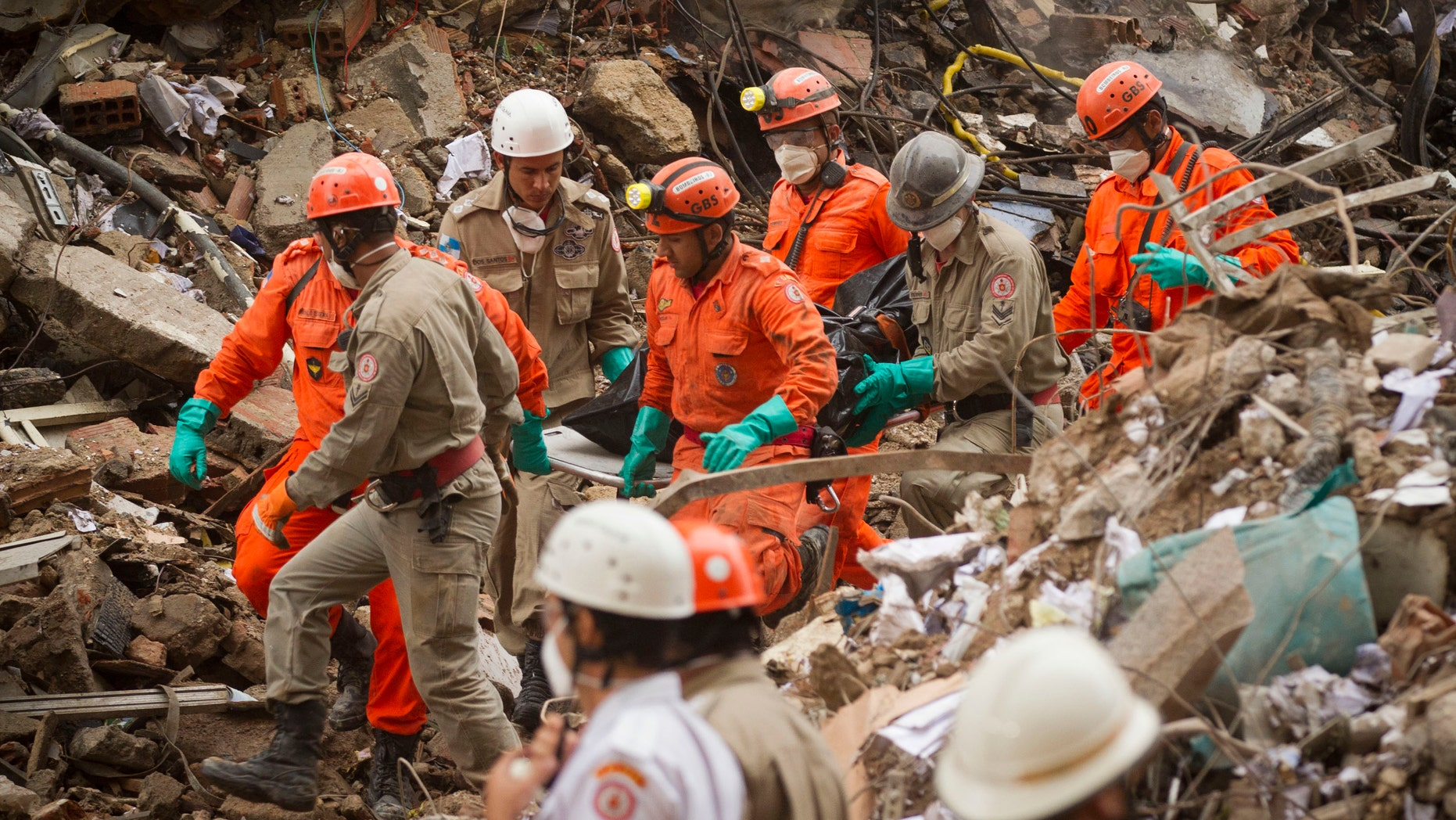 Firefighters carry away a body from the rubble after a building collapsed in downtown Rio de Janeiro, Brazil, Friday Jan. 27, 2012.  The building collapsed on Wednesday, killing at least 9 people and at least 16 are still missing. (AP Photo/Victor R. Caivano)
