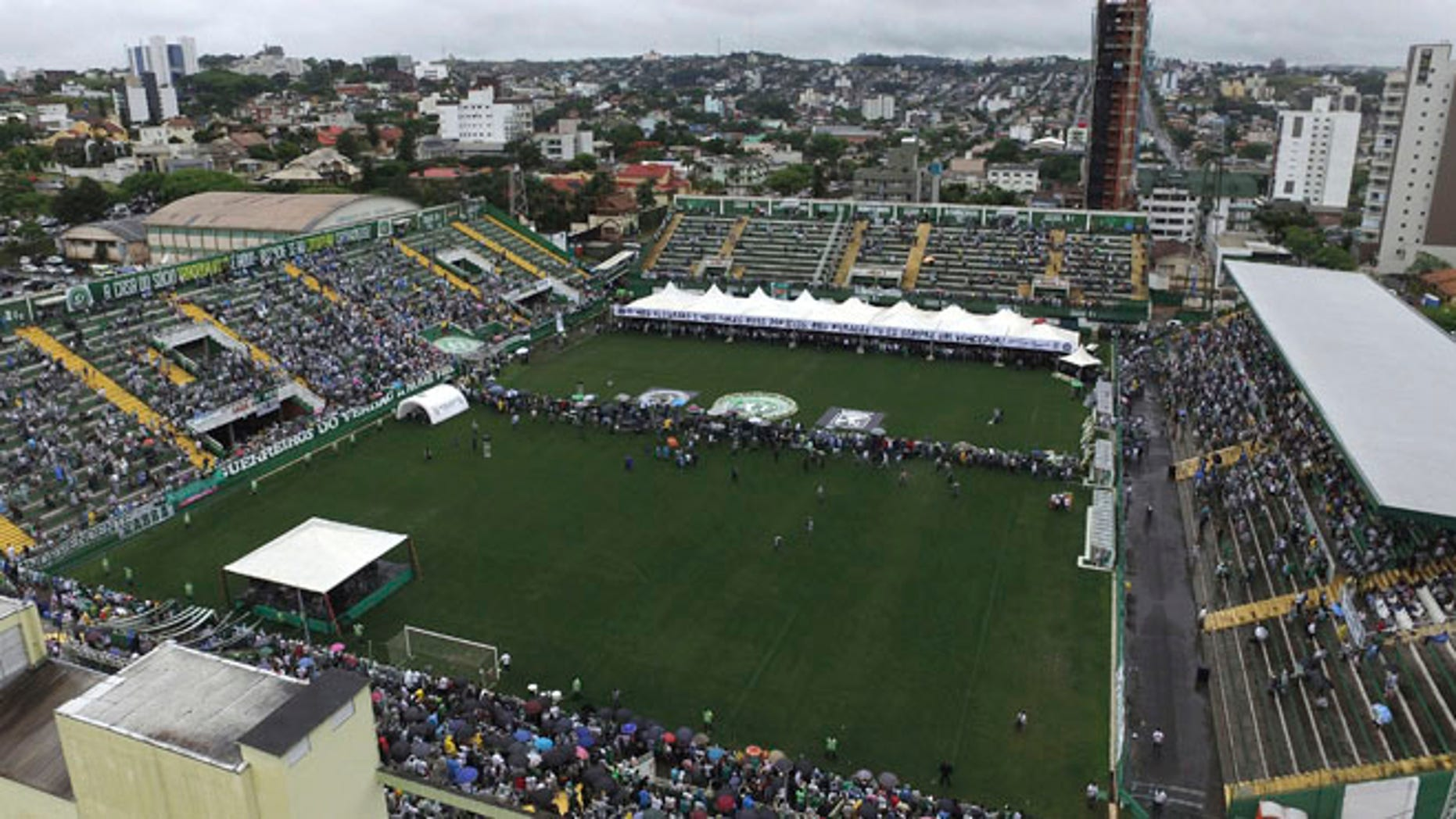 Chapecoense soccer fans attend a memorial for team members who died in a plane crash, at Arena Conda stadium where the caskets stand under the white tarp on the field, in Chapeco, Brazil, Saturday, Dec.3, 2016. The accident Monday in the Colombian Andes claimed most of the team's players and staff as it headed to the finals of one of Latin America's most important club tournaments. (AP Photo/Wesley Santos)