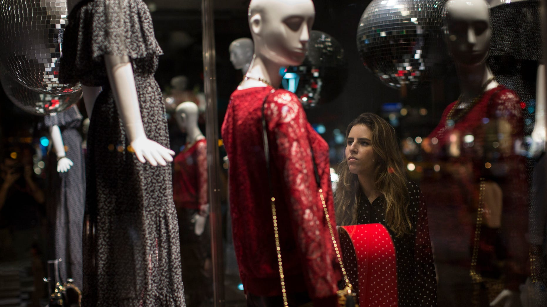 In this Friday, June 12, 2015 photo, a woman is seen through the window of a store as she looks at dresses for sale in Rio de Janeiro, Brazil. Brazilâs top credit information bureaus estimate that as of April, more than 55 million Brazilians were behind on paying off credit cards or loans. Thatâs 37 percent of the adult population in a country of about 200 million people, and the numbers are rising.  (AP Photo/Felipe Dana)