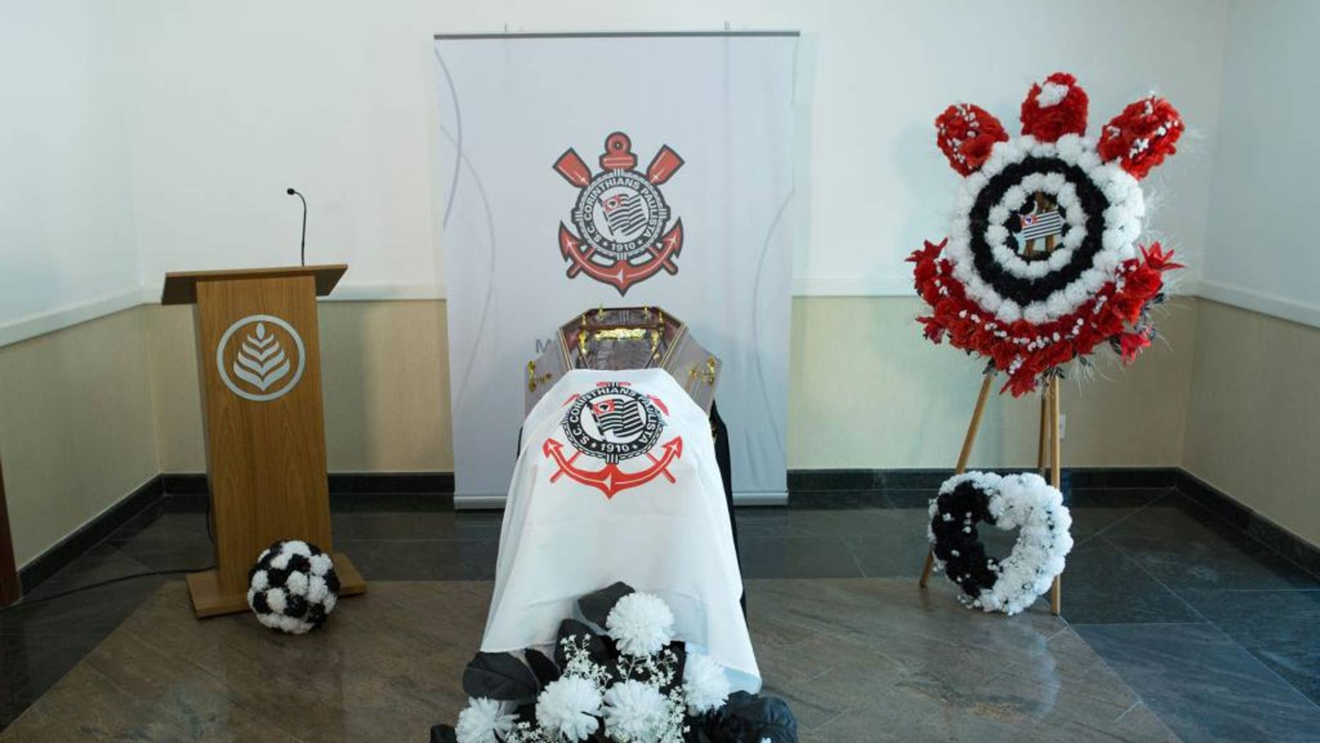 """This undated photo released by the Corinthians soccer team shows an empty casket draped with the team's flag in Sao Paulo, Brazil. Corinthians says it's building its own cemetery, complete with a mock football field and VIP tribunes where some of the team's greatest players will be offered burial spaces. The """"Corinthians Forever"""" cemetery is expected to open late in 2015, but fans can already start booking one of the 70,000 burial places available. (AP Photo/Ivo Duran, Corinthians)"""