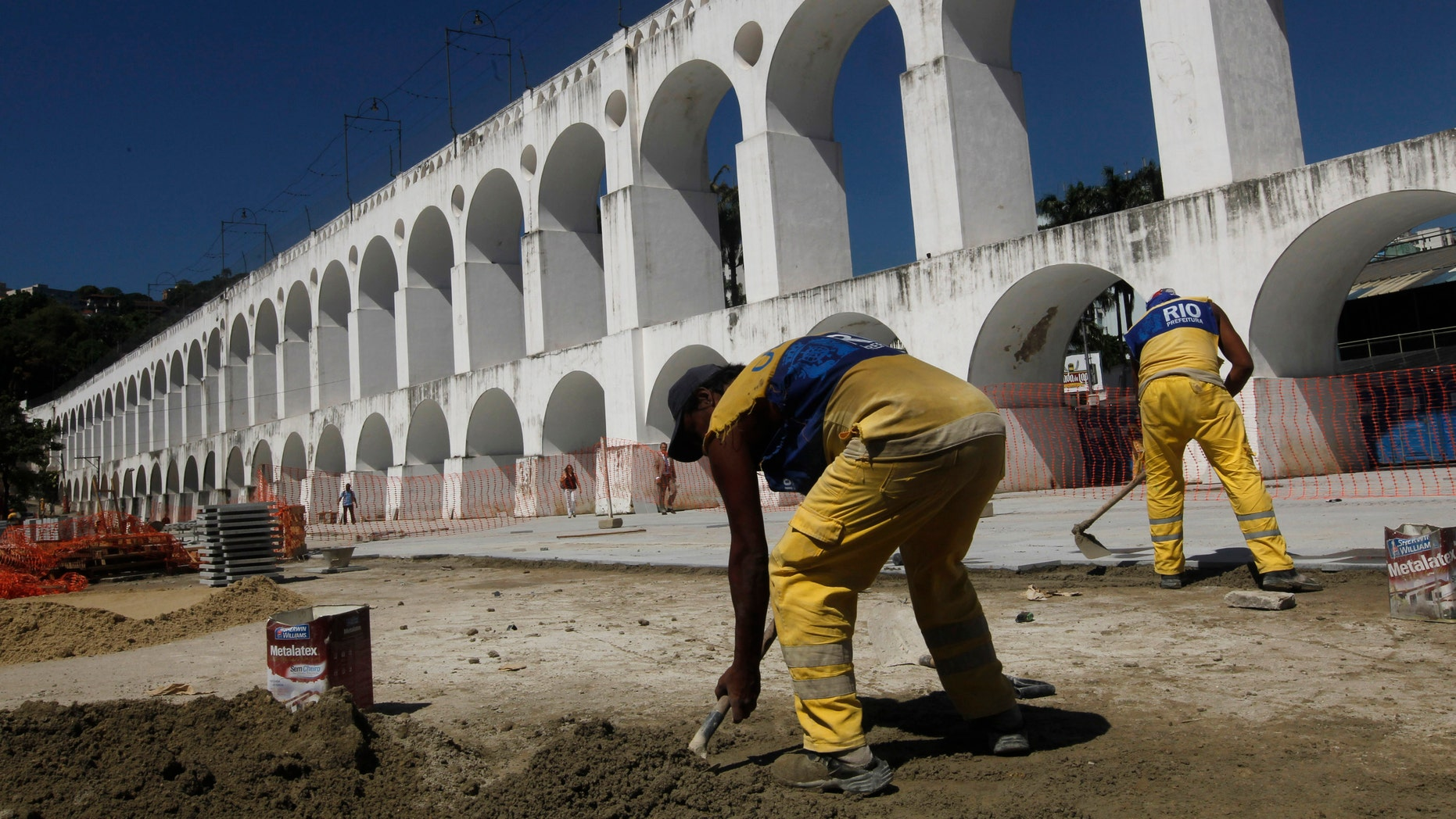 "Workers repave the plaza in front of Rio de Janeiro's ""Arcos da Lapa,"" an aqueduct converted into a trolley bridge, on Feb. 1. In the past year, a trolley car ran off the arches' rails, killing five. These accidents are contributing to a growing concern about Rio de Janeiro's readiness to host the finals of the 2014 World Cup as well as the 2016 Olympics. (AP Photo/Silvia Izquierdo)"
