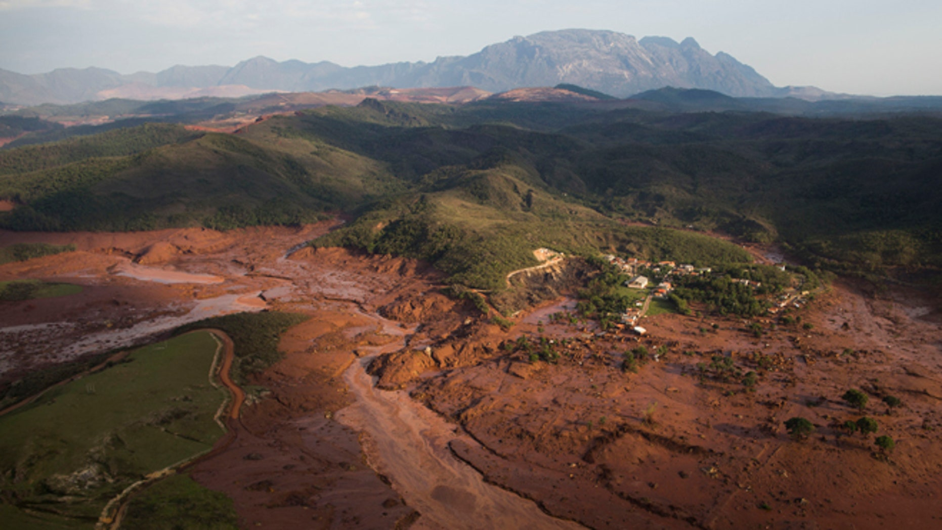 Aerial view of the debris and mud on Thursday, at the small town of Bento Rodrigues after a dam burst in Minas Gerais state, Brazil, Friday, Nov .6, 2015.  Brazilian rescuers searched feverishly Friday for possible survivors after two dams burst at an iron ore mine in a southeastern mountainous area.  (AP Photo/Felipe Dana)