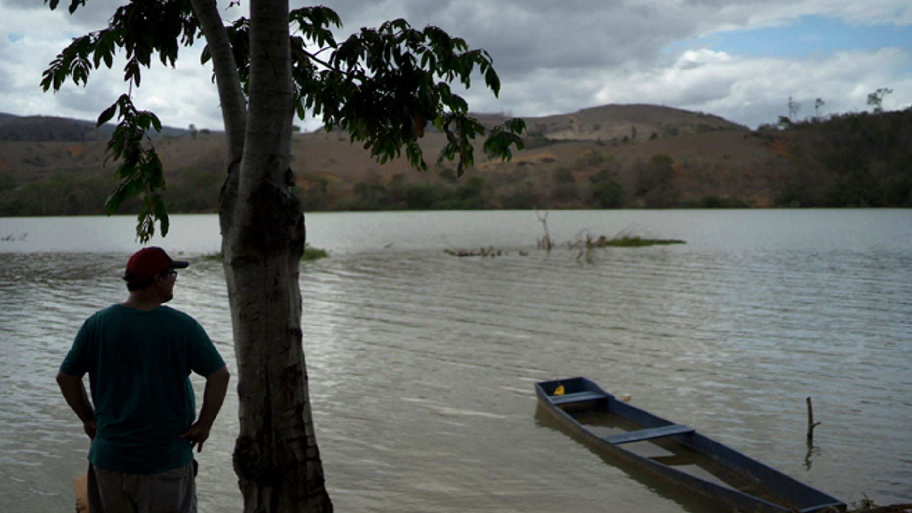 """In this Oct. 11, 2016 photo, fisherman Deucimar Teixeira Lordes stands on the banks of the Doce River, in Mascarenhas, Brazil. The 45-year-old fisherman has doubts that he will fish in the Doce again. """"Fishing here is not good anymore. I would not eat it and I don't have courage to sell it to the people."""" Lordes said. (AP Photo/Leo Correa)"""