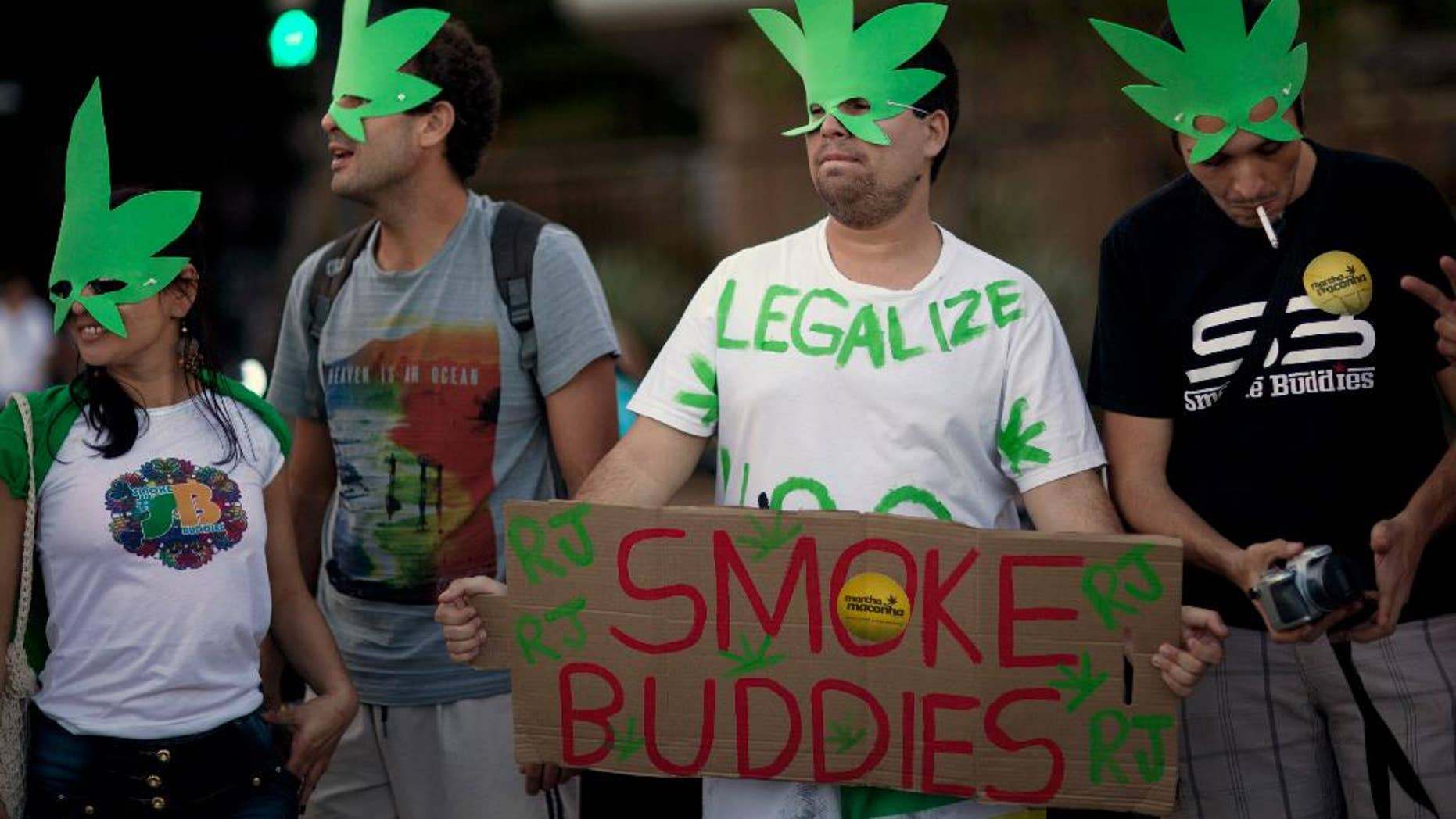 FILE - In this May 11, 2013 file photo, demonstrators wear cannabis shaped masks to support the legalization of marijuana in Rio de Janeiro, Brazil, during a march marking the 32 anniversary of Jamaican musician Bob Marley's death. Brazil's Supreme Court on Wednesday, Aug. 19, 2015 began debating a drug case that could lead to the decriminalization of drug possession for personal use. A final ruling is not expected for several days. (AP Photo/Felipe Dana, File)