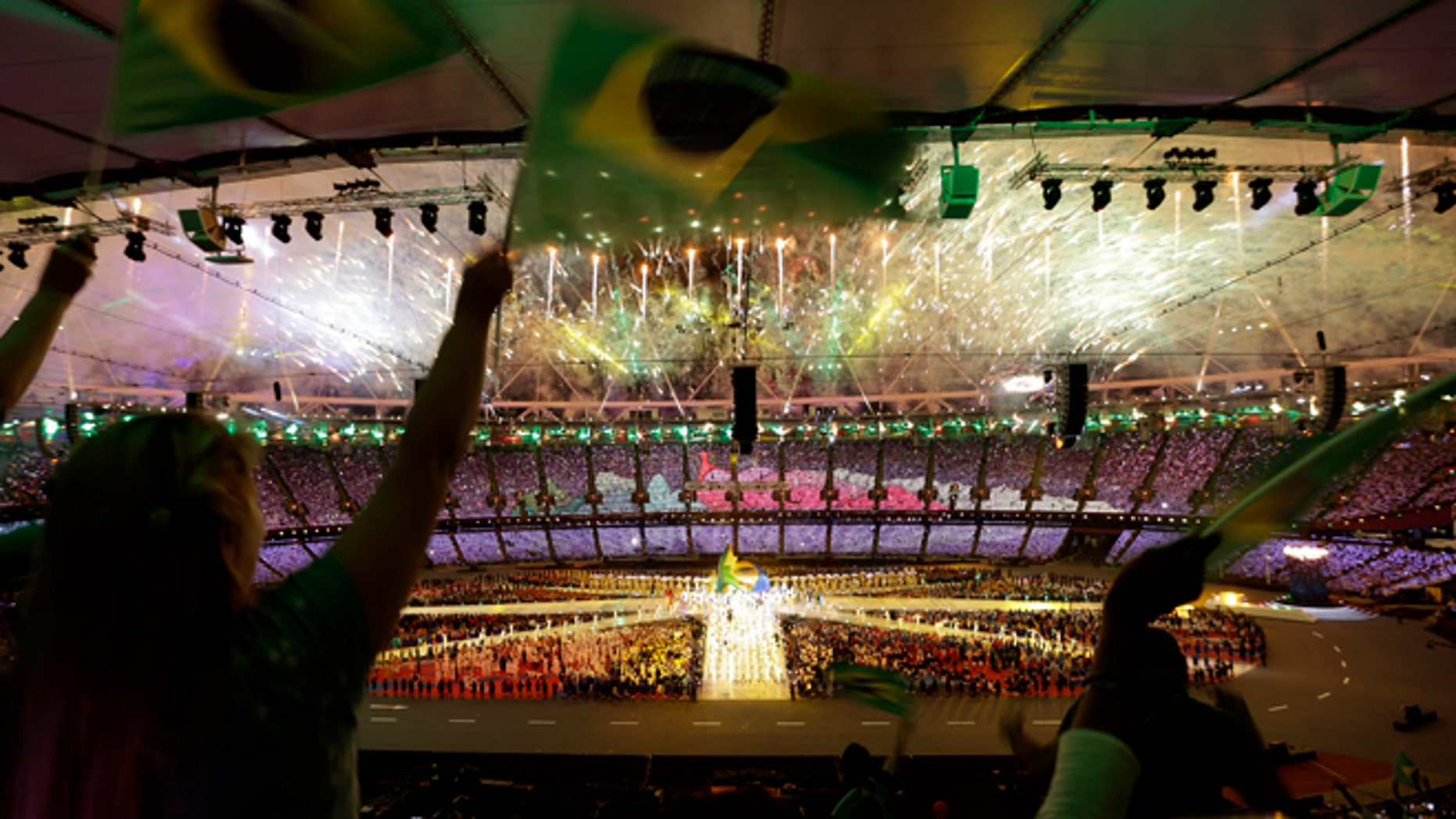 Spectators wave Brazilian flags as fireworks explode over the Olympic stadium during the Closing Ceremony at the 2012 Summer Olympics, Sunday, Aug. 12, 2012, in London. (AP Photo/Hassan Ammar)