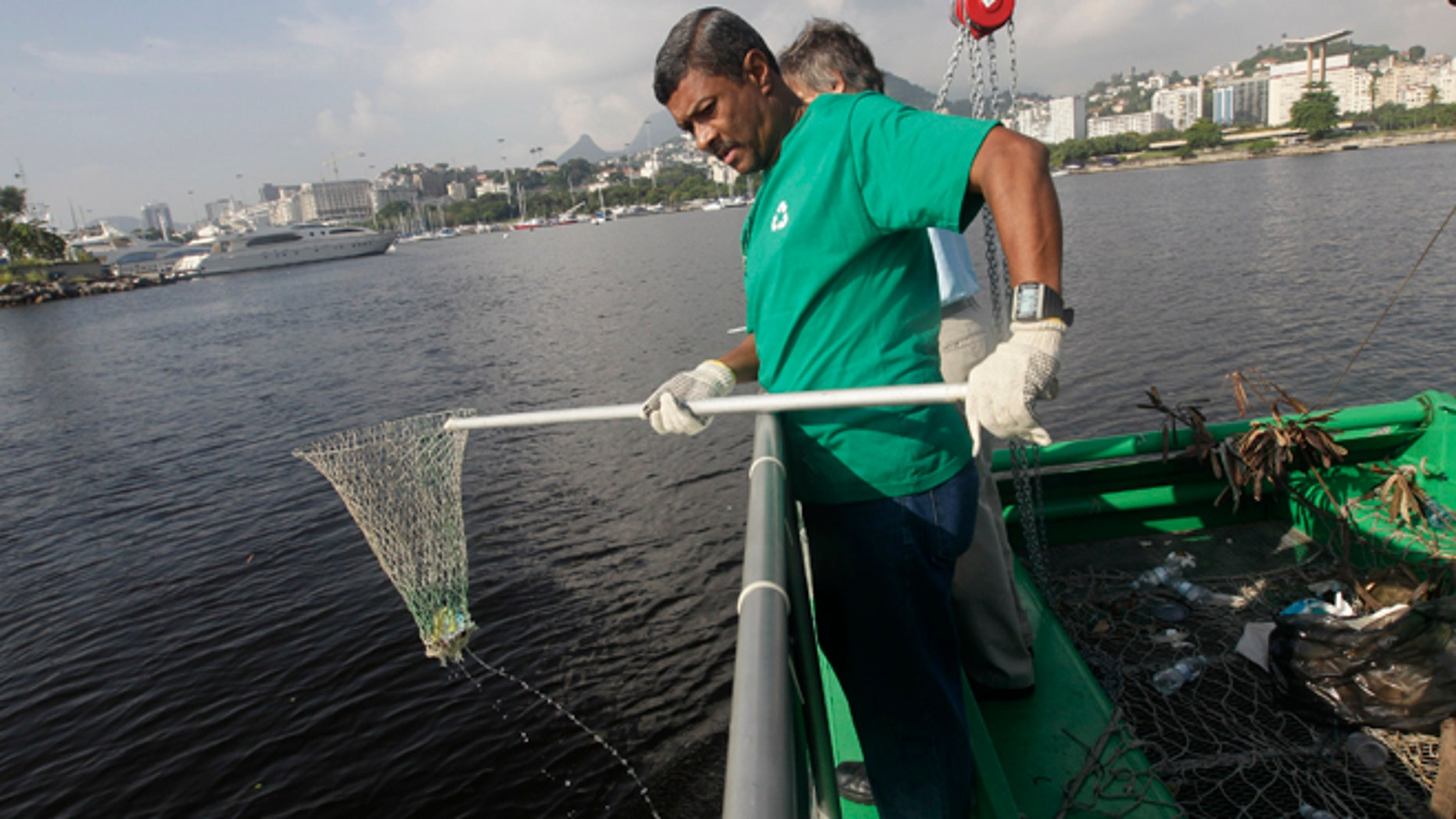 """A worker fishes out trash from a garbage-collecting barge at the Guanabara bay, in Rio de Janeiro, Brazil, Monday, Jan. 6, 2014. The green barge plies the polluted waters of Rio de Janeiroâs Guanabara Bay alongside wooden fishing boats but its catch consists not of grouper or swordfish but rather plastic bags, empty soda bottles and a discarded toilet seat. The barge is one of three so-called """"eco-boats,"""" floating garbage vessels that are a key part of authorities' pledge to clean up Rioâs devastated Guanabara Bay before the city â and the waterway itself â plays host to the 2016 Olympic games. (AP Photo/Silvia Izquierdo)"""