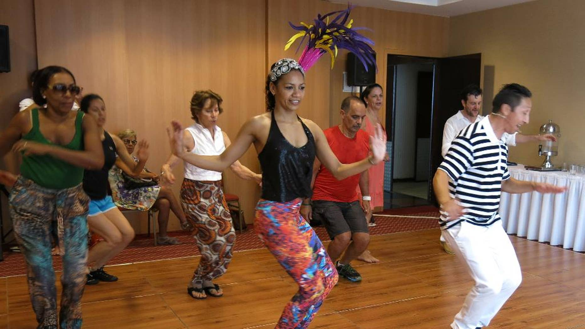 Nete Vieira, center, and her husband Naldi, right, teach samba to foreigners in Rio de Janeiro, Sunday, Feb. 15, 2015. There is a self-deprecating phrase Brazilians with poor dancing skills use to explain their awkwardness at the parades during Carnival: I samba like a foreigner. But even foreigners visiting Brazil for Carnival celebrations can learn a few basic moves thanks to the patience of dancing duo Nete Vieira and her husband Naldi. They teach the basics of rhythmic bouncing, marching and arm waving that will help newcomers have fun, and feel less intimidated, while joining the raucous parties that crowd the streets of Rio de Janeiro. (AP Photo/Adriana Gomez)