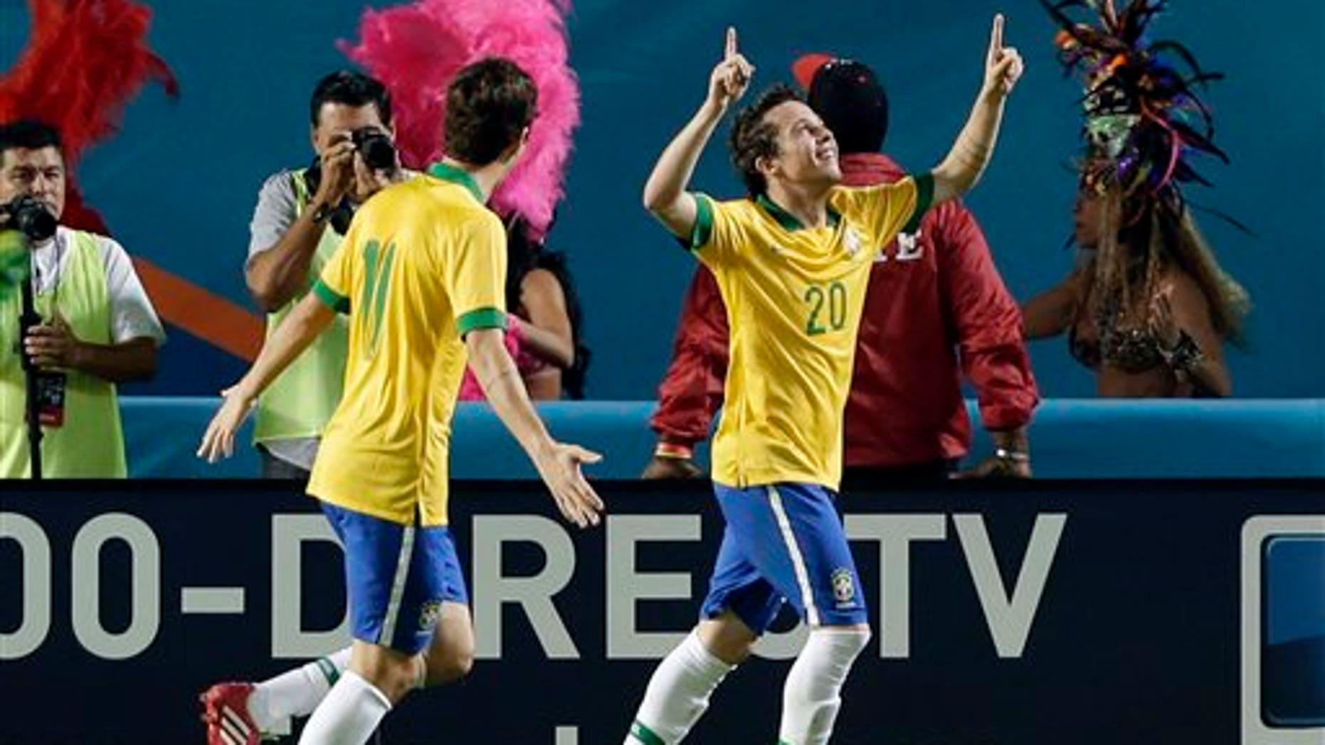 Brazil forward Bernard (20) celebrates his goal with midfielder Oscar (11) during the first half of an international friendly soccer game against Honduras, Saturday, Nov. 16, 2013, in Miami Gardens, Fla. (AP Photo/Wilfredo Lee)