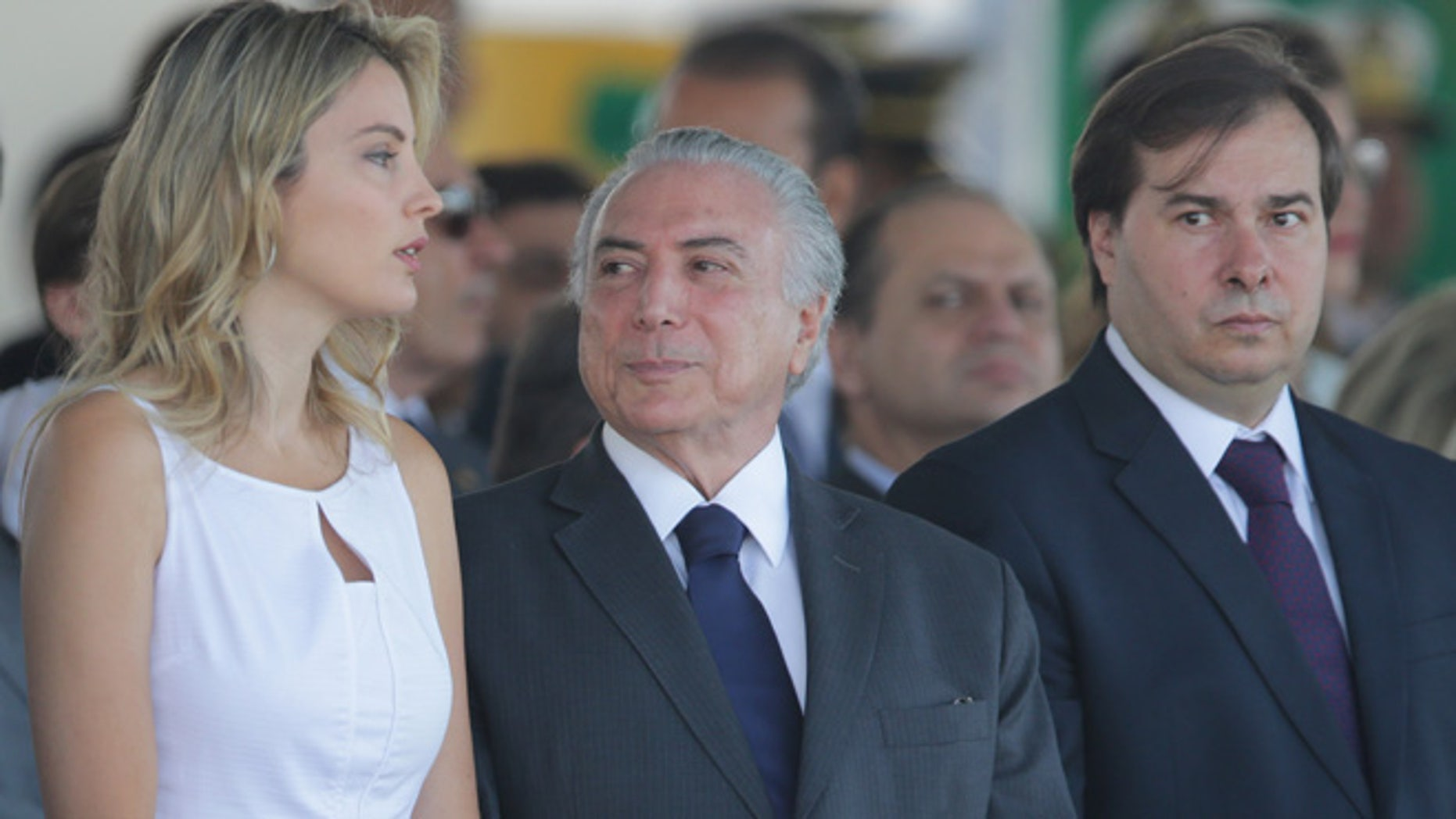 Brazil's President Michel Temer, center, talks with his wife Marcela Temer, during an Independence Day military parade in Brasilia, Brazil, Wednesday, Sept. 7, 2016. Pictured right is Lower House Speaker Rodrigo Maia. (AP Photo/Eraldo Peres)