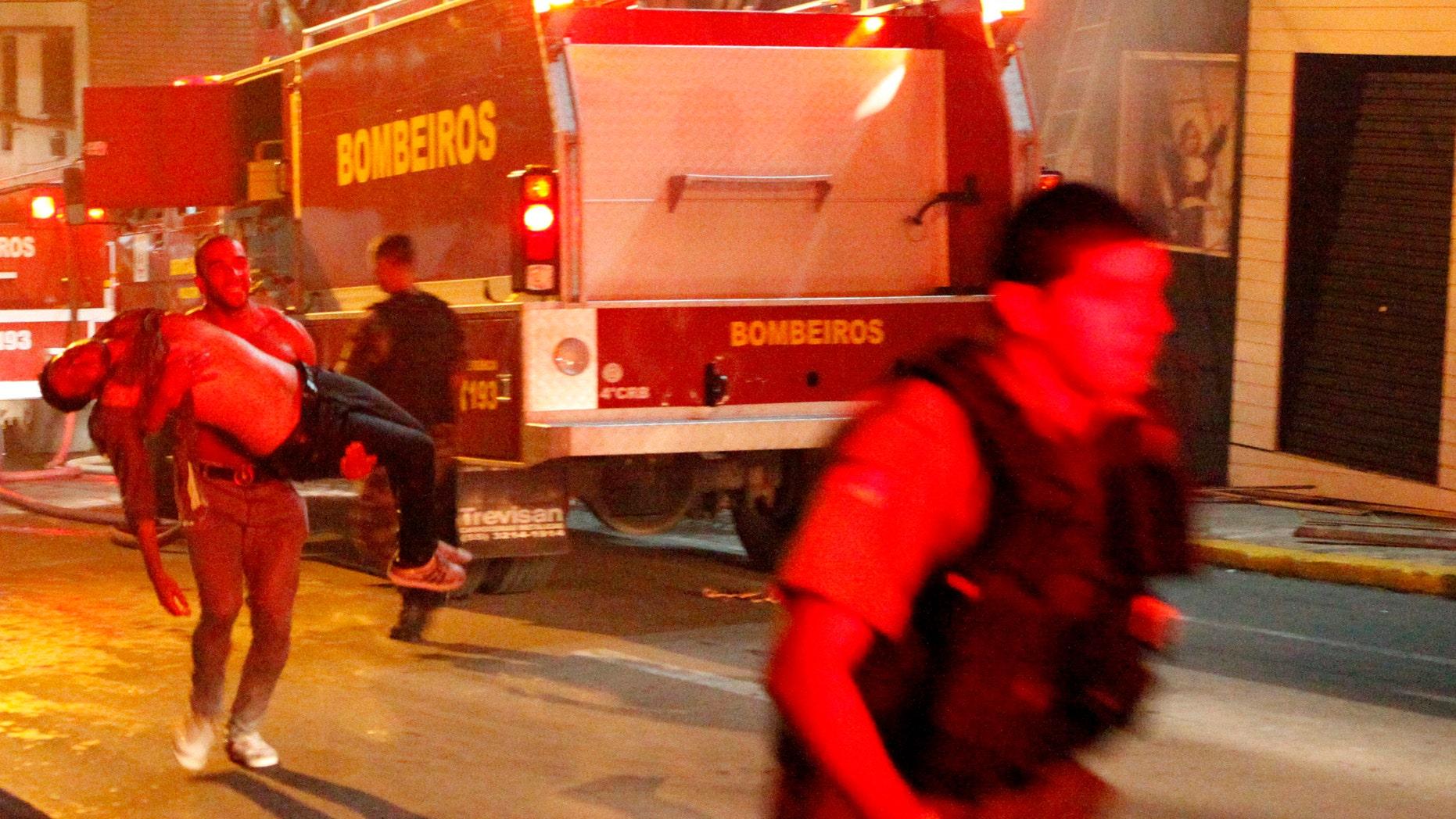 A man carries an injured man, victim of a fire at the Kiss  club in Santa Maria city,  Rio Grande do Sul state, Brazil, early Sunday, Jan. 27, 2013.  (AP Photo/Agencia RBS)