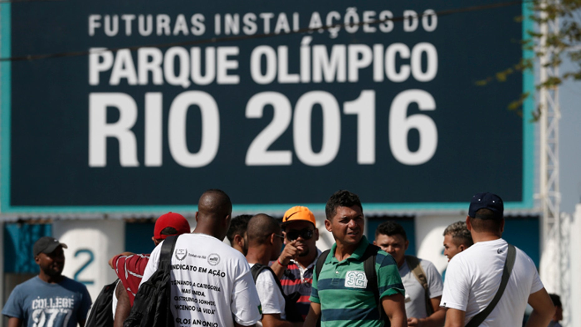 Striking workers stand in front the entrance of the Olympic Park, the main cluster of venues under construction for the 2016 Summer Olympic Games, in Rio de Janeiro, Brazil, Tuesday, April 8, 2014. The labor dispute centers around which union represents the construction workers, and also involves benefits and working conditions. (AP Photo/Silvia Izquierdo)