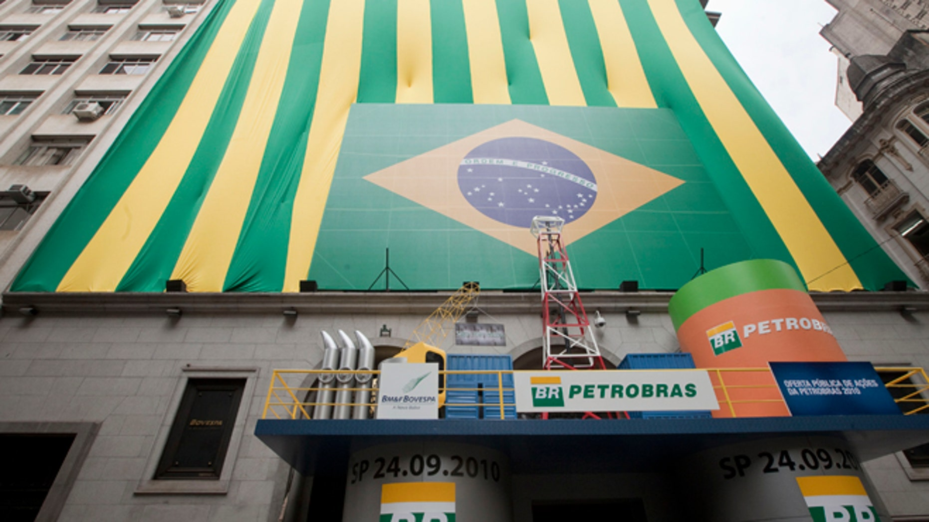 """FILE - In this Sept. 24, 2010 file photo, a Brazilian flag and the word """"Petrobras"""" decorate the entrance of the stock market building on the first day of trading in Sao Paulo, Brazil. Brazils Attorney General Rodrigo asked the nations Supreme Court on Tuesday, March 3, 2015 for permission to investigate top political figures for alleged involvement in a kickback scheme at the state-run oil company Petrobras, which prosecutors say is the countrys largest corruption scandal yet uncovered. (AP Photo/Andre Penner, File)"""