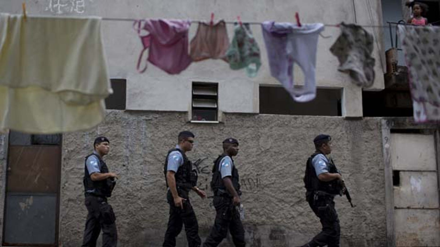 July 21, 2013: Policemen from the Pacifying Police Unit, or 'UPP', patrol in the Varginha area of the Manguinhos slum complex where Pope Francis will visit next week during his trip to Rio de Janeiro, Brazil (AP Photo)