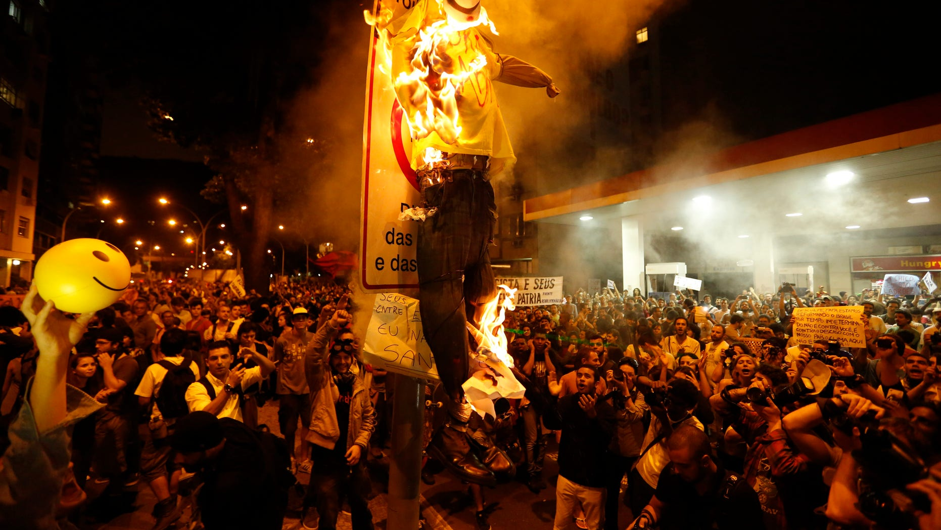 Protesters burn a puppet that symbolizes Rio de Janeiro State Governor Sergio Cabral during a demonstration near Guanabara Palace in Rio de Janeiro, Brazil, Monday, July 22, 2013.