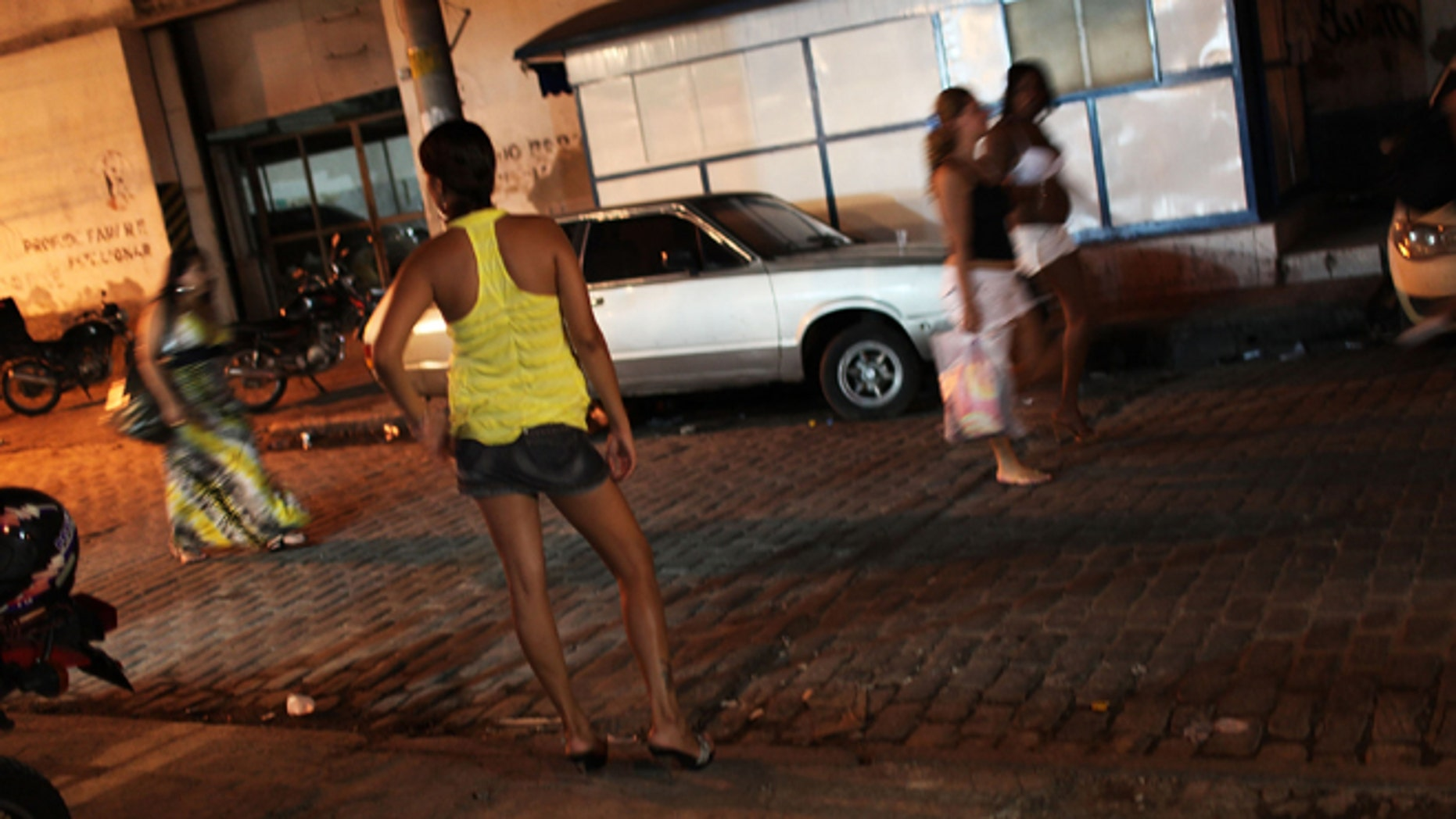 RIO DE JANEIRO, BRAZIL - DECEMBER 11: Female prostitutes walk the streets of the red light district, Vila Mimosa, following a fashion show with clothes designed by sex workers on December 11, 2009 in Rio de Janeiro, Brazil. The fashion show, which is a government sponsored project to give female prostitutes other career choices, displayed dozens of new designs on both models and three fellow prostitutes. The Association of the Residents and Friends of Vila Mimosa teaches the women skills in sewing and design. Out of the 105 woman to enroll in the fashion design program 65 have now found jobs in other professions besides working in the sex industry.  (Photo by Spencer Platt/Getty Images)