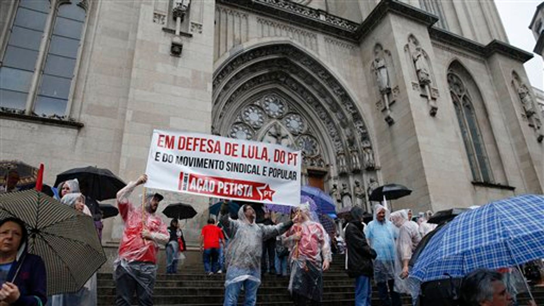 Demonstrators gather on the cathedral steps to show support for former Brazil's President Luiz Inacio Lula da Silva, in Sao Paulo, Brazil, Friday, March 11, 2016.  Sao Paulo state prosecutors said Thursday they filed money laundering and criminal misrepresentation charges against the former leader because of evidence he and his family unduly benefited from a real estate scheme that adversely affected thousands of Brazilian families. (AP Photo/Andre Penner)