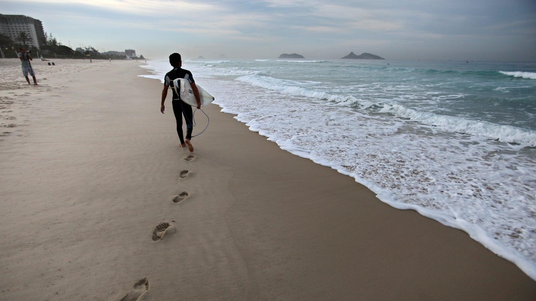 A surfer walks next to the shore at Barra da Tijuca beach before the start of the Billabong Rio Pro surfing championship in Rio de Janeiro, Brazil, Thursday, May 12, 2011. (AP Photo/Victor R. Caivano)