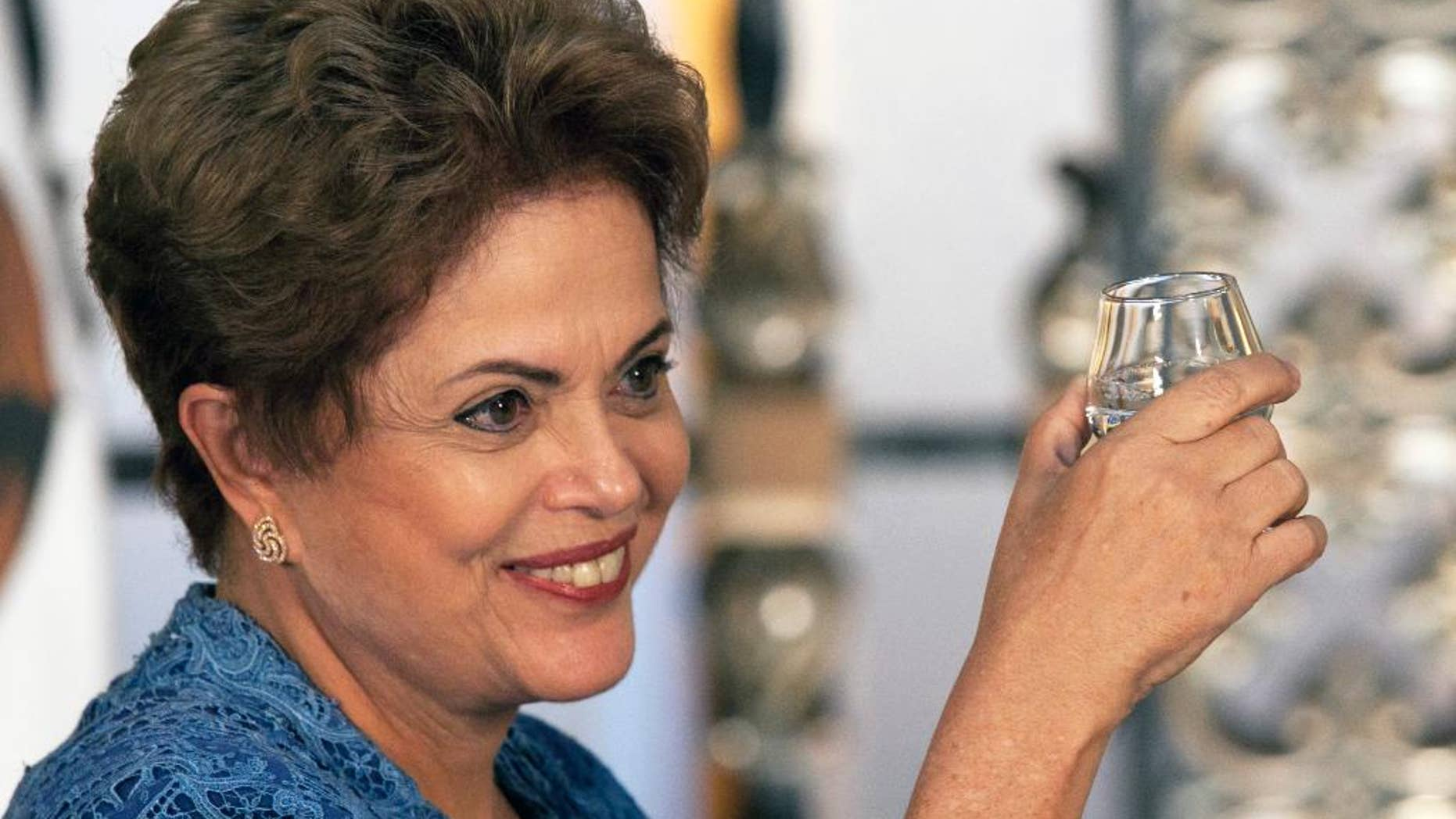 FILE - In this May 26, 2015, file photo, Brazil's President Dilma Rousseff raises her cup during a toast with Mexico's President Enrique Pena Nieto, not in photo, during an official ceremony at the National Palace in Mexico City. Rousseff's popularity ratings have dropped to levels not seen since the government of disgraced former president Fernando Collor de Mello in 1992, according to a poll published Sunday, June 21. (AP Photo/Marco Ugarte, File)