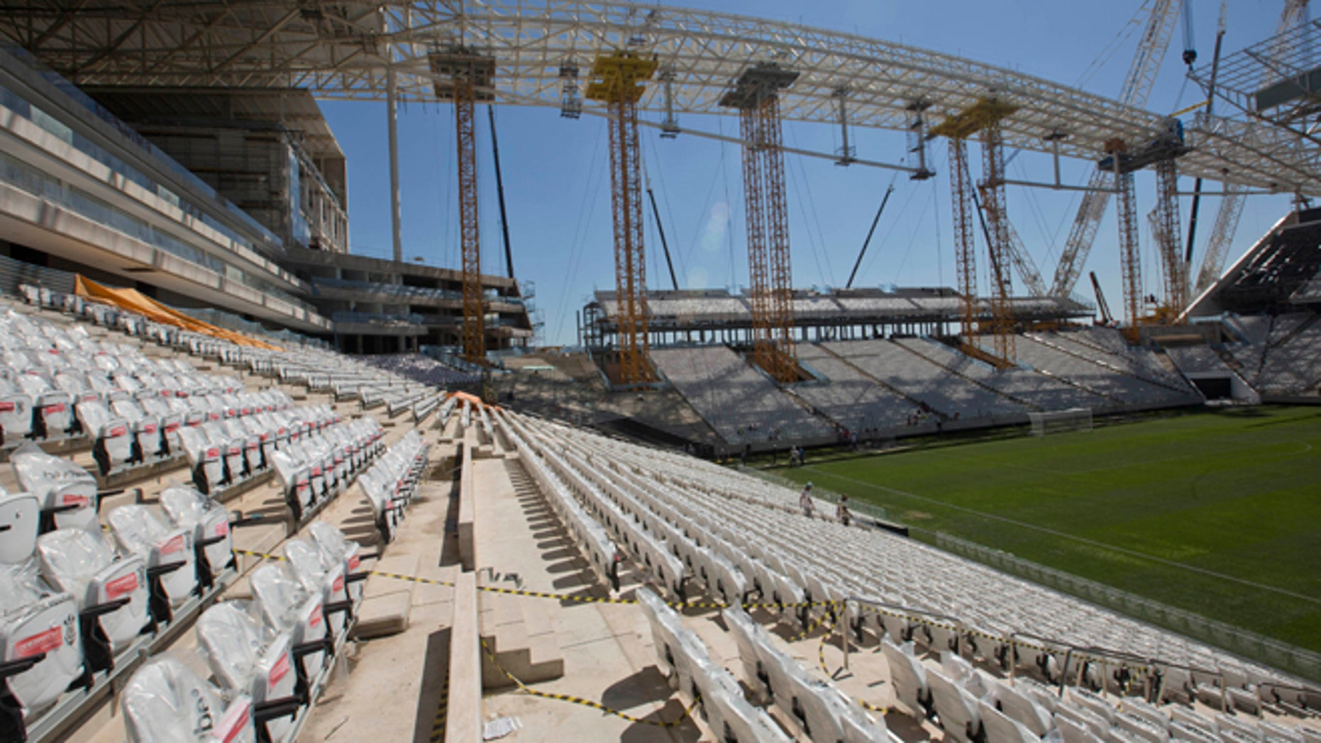 Men work at the Itaquerao, the stadium that will host the World Cup opener in less than three months in Sao Paulo, Brazil, Saturday, March 15, 2014. The Itaquerao was one of the six stadiums that were supposed to be finished by the end of 2013, but a crane collapse that killed two workers in November caused significant delays to the venue where Brazil will play Croatia on June 12. The stadium is not expected to be ready before mid-April. (AP Photo/Andre Penner)