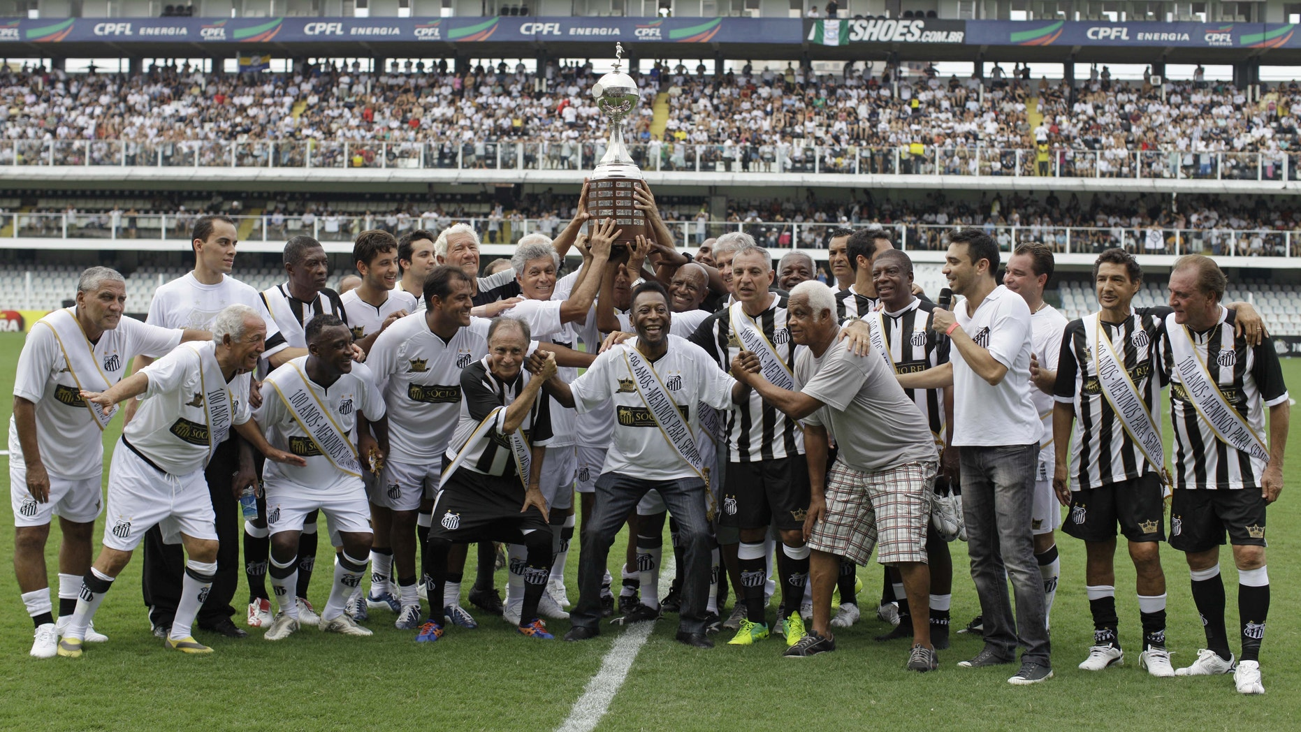 """Pelé, center, with other former Santos soccer players hold up the Libertadores championship trophy during during the centennial anniversary celebration of the team in Santos, Brazil, Saturday, April 14, 2012. Santos, the Brazilian club which ruled football with """"The King"""" Pele in the 1960's, turns 100 with a rich history to show, including many major titles and remarkable victories that make the club one of the most successful in football. (AP Photo/Nelson Antoine)"""