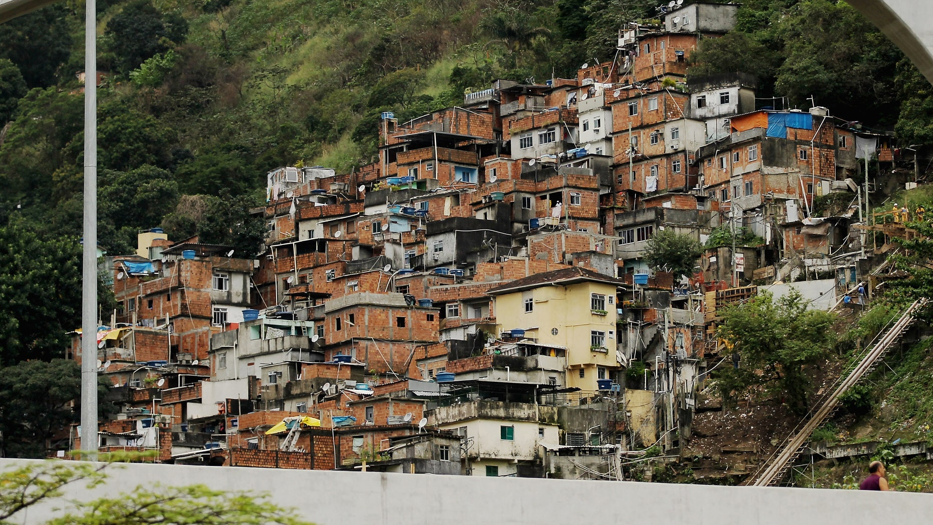 "A ""pacified"" favela, or squatter settlement, is seen on a forested hillside on June 21, 2012 in Rio de Janeiro, Brazil. Rio de Janieroâs authorities have successfully ""pacified"" a number of formerly crime-ridden favelas in the city.  (Photo by Mario Tama/Getty Images)"