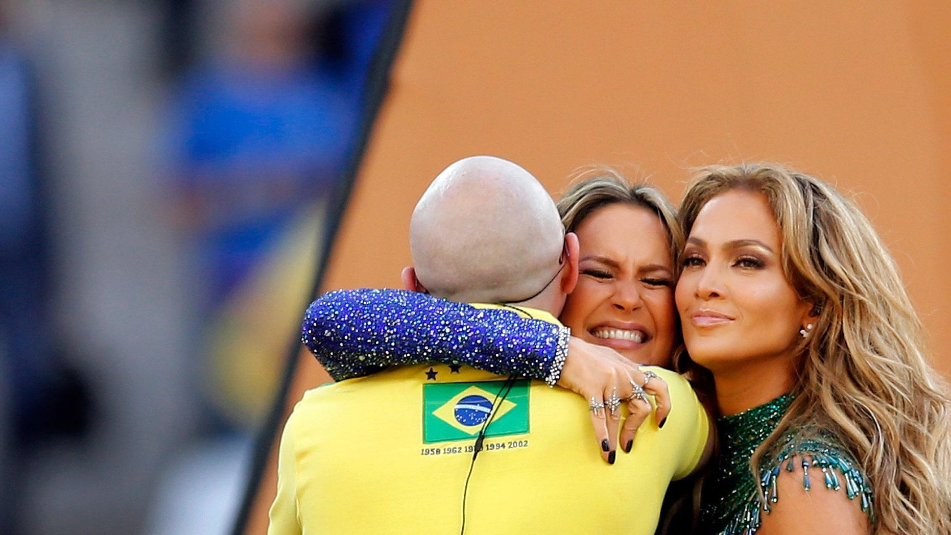 Brazilian singer Claudia Leitte embraces Jennifer Lopez and Pitbull in the Itaquerao Stadium in Sao Paulo, June 12, 2014.