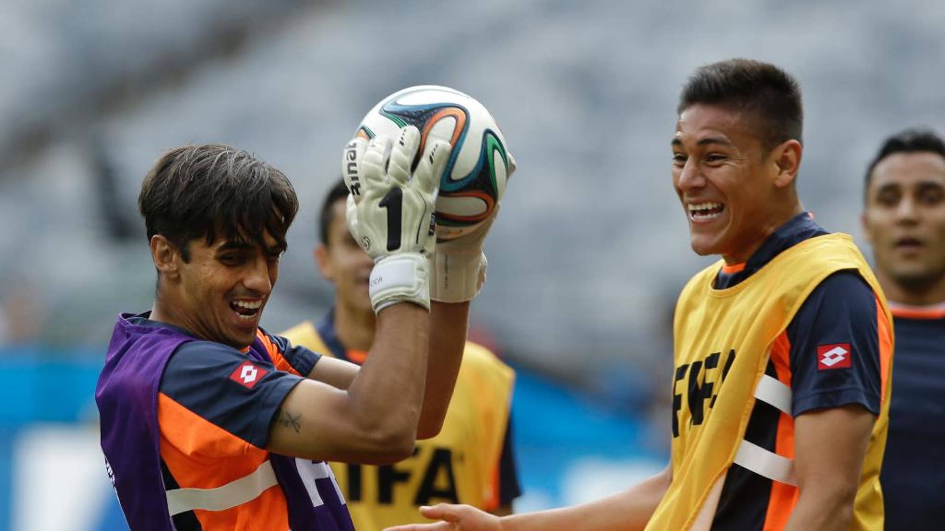 Costa Rica's captain and attacking player Bryan Ruiz, left, catches the ball whilst playing as a goalkeeper during an official training session the day before the group D World Cup soccer match between Costa Rica and England at the Mineirao Stadium in Belo Horizonte, Brazil, Monday, June 23, 2014. (AP Photo/Matt Dunham)