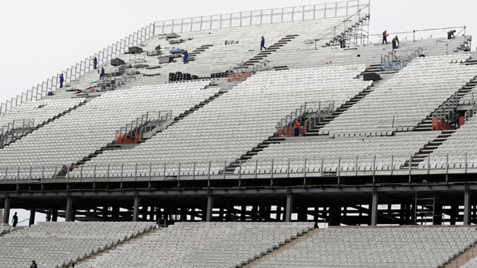 Laborers work on the construction of the Itaquerao stadium in Sao Paulo, Brazil, Tuesday, April 22, 2014. FIFA Secretary General Jerome Valcke said Tuesday there's still a lot of work to do at the stadium, but added that it will be ready for the opening match between Brazil and Croatia in June. (AP Photo/Andre Penner)