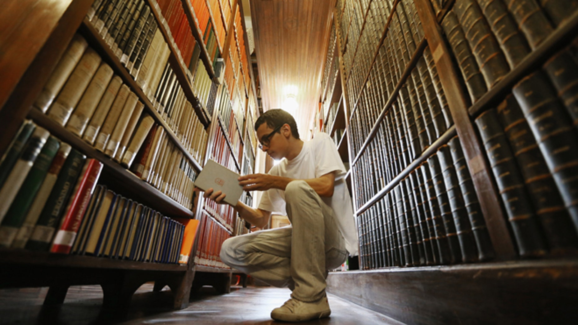 SAO PAULO, BRAZIL - MARCH 12:  Philosphy student Sergio Araujo sorts books in a 19th-century library inside Sao Bento Monastery on March 12, 2013 in Sao Paulo, Brazil. The monastery is said to be the oldest institution in Sao Paulo; Benedictines arrived at the site in 1598. Pope Benedict XVI visited Sao Bento in 2007. Brazil has more Catholics than any other country in the world and supporters hope Sao Paulo Archbishop Cardinal Odilo Pedro Scherer will be chosen as the next Pope during the papal conclave.  (Photo by Mario Tama/Getty Images)