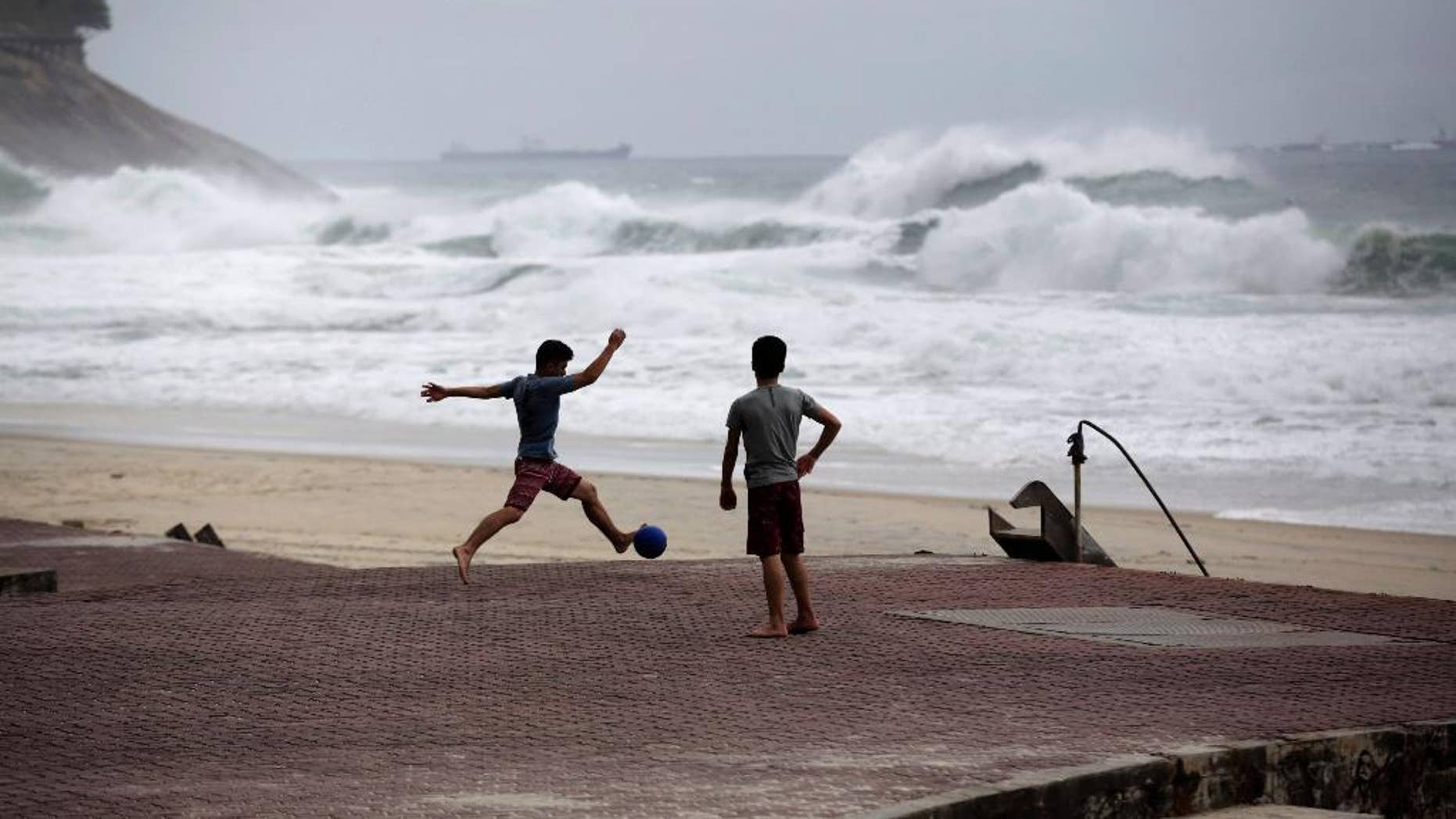 "FILE - In this June 20, 2014 file photo, boys play football as waves break on Sao Conrado beach in Rio de Janeiro, Brazil. World Surf League spokesman Dave Prodan said in an emailed statement Wednesday, April 29, 2015, that Sao Conrado beach had to be removed from its venue list ""due to pollution issues."" The beach had been a backup for the May 11-22 Rio Pro event, to be used in case of sub-par waves or other issues at the primary venue, nearby Barra da Tijuca beach. (AP Photo/Matt Dunham, File)"