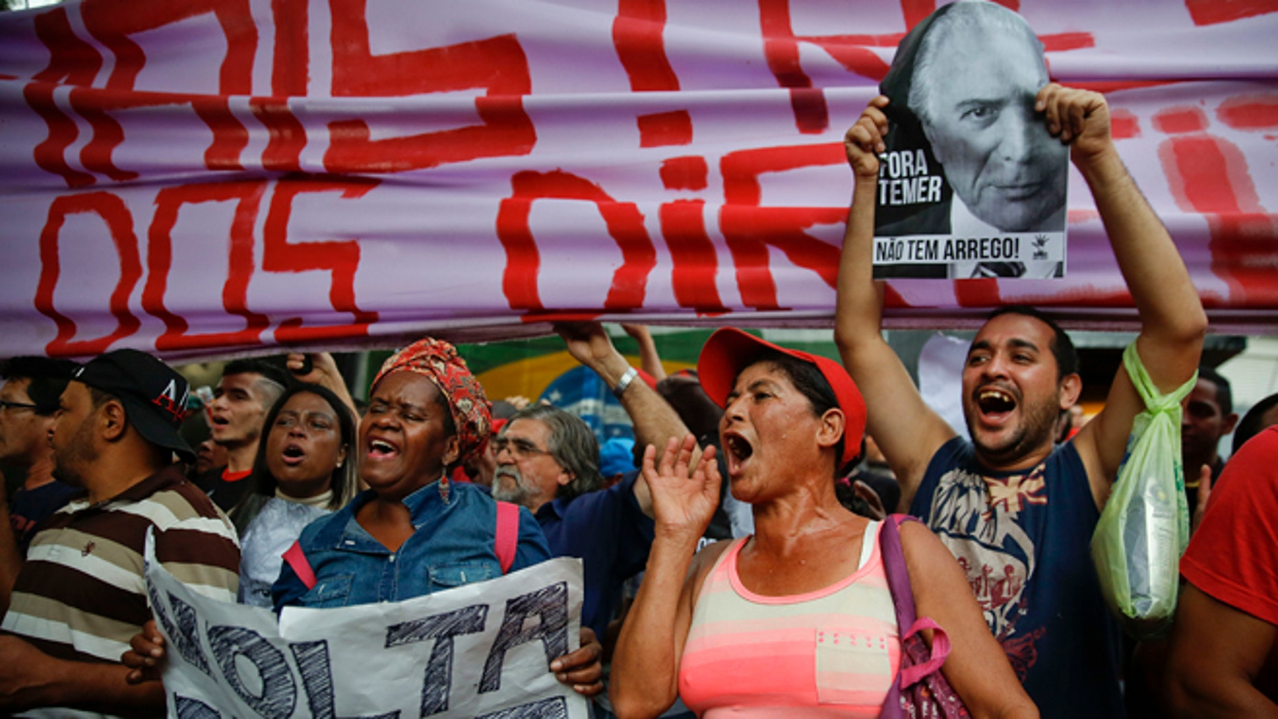 """With signs that read in Portuguese """"Dilma come back"""" and """"Temer Out,"""" demonstrators shout slogans during a protest against Brazil's acting President Michel Temer and in support of Brazil's suspended President Dilma Rousseff, close to Temer's residence in São Paulo, Brazil, Sunday, May 22, 2016. Temer took office after Rousseff was suspended for up to 180 days while the Senate holds an impeachment trial. (AP Photo/Andre Penner)"""