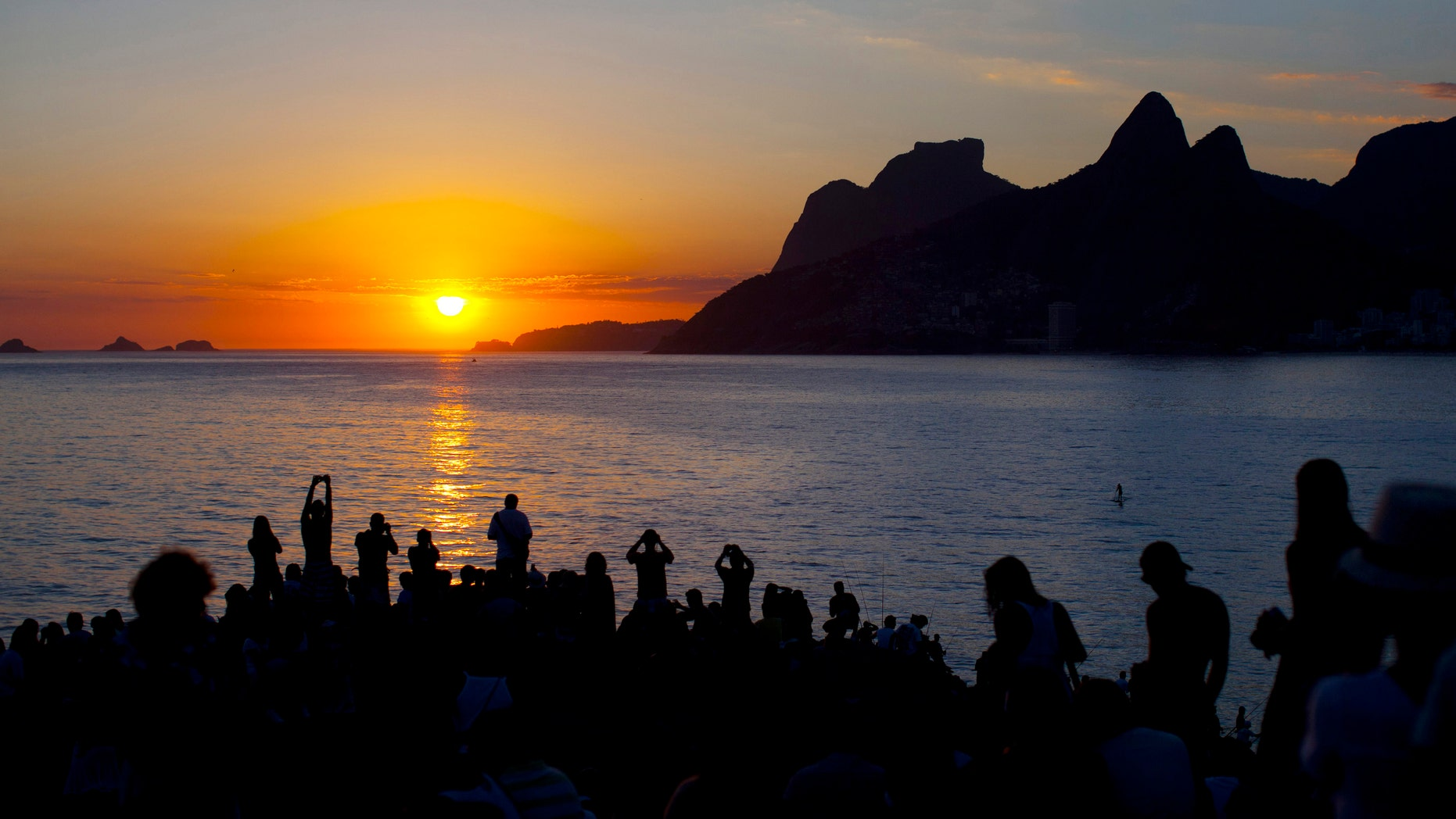 In this photo taken on Feb. 6, 2012, people watch the sun set and take pictures from Arpoador beach in Rio de Janeiro, Brazil. Rio is a city of contrasts, where vastly different worlds rub shoulders, and the unexpected lies lurking around every corner.  (AP Photo/Felipe Dana)