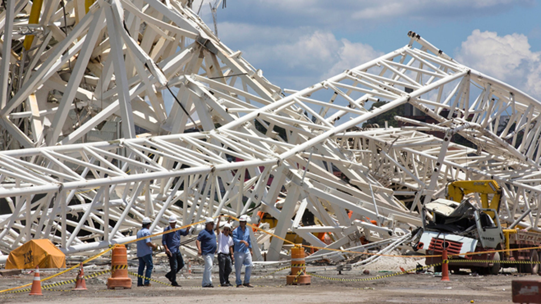 Civil defense and policemen inspect the damage of an accident at the Arena Corinthians, known locally as the Itaquerao, that will host the 2014 World Cup in Sao Paulo, Brazil, Thursday, Nov. 28, 2013. Two workers were killed when a crane crashed into a 500-ton metal structure that toppled over part of the stadium Wednesday, aggravating already urgent worries that Brazil won't be ready for soccer's showcase event next year. (AP Photo/Andre Penner)