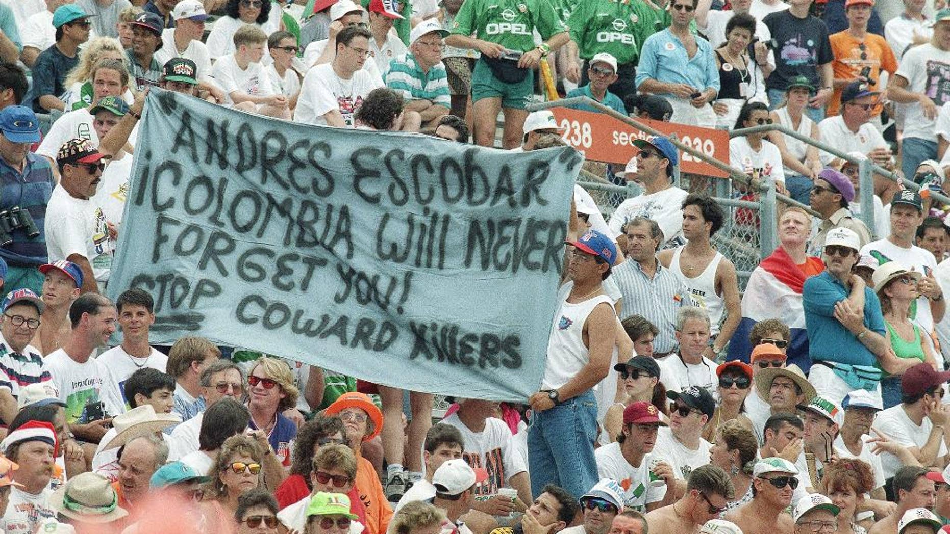 FILE - In this July 4, 1994, file photo, Fans at the World Cup match between Netherlands and Ireland hold up a banner at Orlando's Citrus Bowl in Orlando, Florida, referring to Colombian soccer player Andres Escobar who was murdered in Medellin, Colombia, after his team lost to the United States in the first round of World Cup.  The murder of Escobar 20 years ago Wednesday after he accidentally scored a goal for the other side and helped eliminate his team from the World Cup stands in stark contrast to the national squad's celebrated success in this 2014 Soccer World Cup in Brazil. (AP Photo/Lynne Sladky, File)