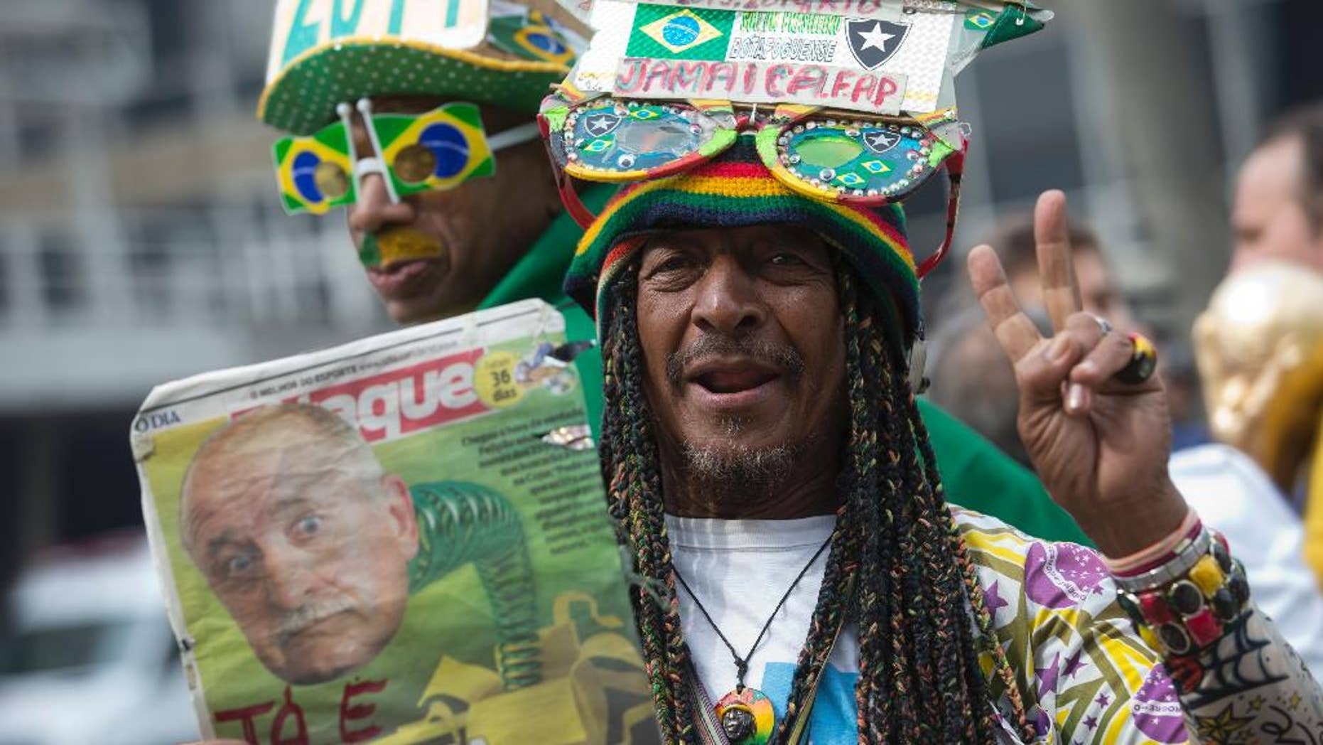 A Brazil soccer fan holds up a newspaper with a photo of Brazil's coach Luiz Felipe Scolari and flashes a victory sign outside the venue where coach Luiz Felipe Scolari is announcing his squad for the upcoming international soccer tournament in Rio de Janeiro, Brazil, Wednesday, May 7, 2014. The team will mix talented young stars such as Neymar and Oscar with more experienced players such as Dani Alves, David Luiz, Thiago Silva and Hulk. Past stars such as Ronaldinho, Kaka and Robinho were left off the squad as expected. (AP Photo/Silvia Izquierdo)
