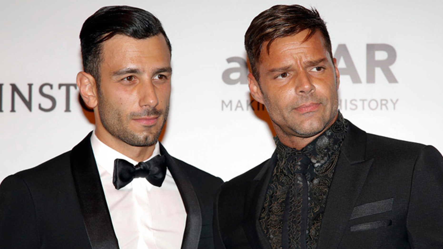 Singer Ricky Martin, right, and artist Jwan Yosef pose on the red carpet of The Foundation for AIDS Research (amfAR) event in Sao Paulo, Brazil, Friday, April 15, 2016. (AP Photo/Andre Penner)