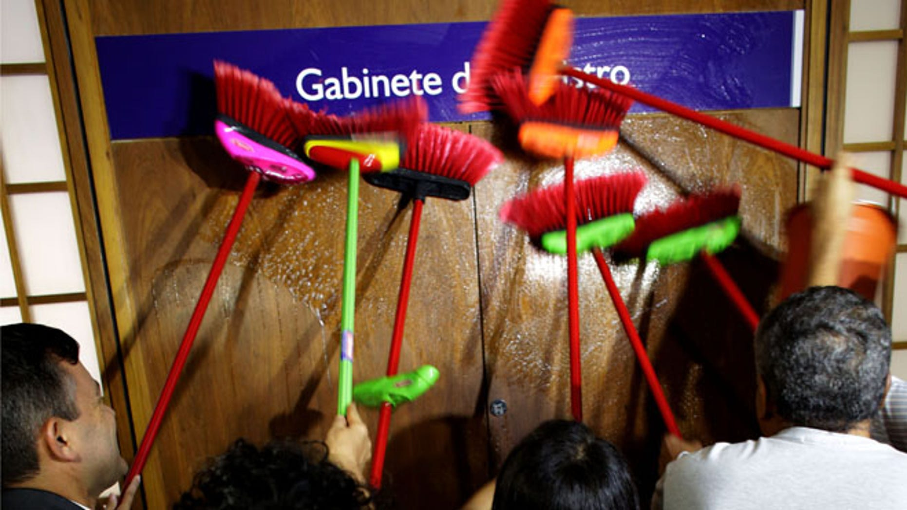 Ministerial staff use brooms to scrub the office door of the Transparency Minister Fabiano Silveira demanding his resignation, in Brasilia, Brazil, Monday, May 30, 2016. A recording TV Globo broadcast late Sunday shows Silveira criticizing Operation Car Wash, a wide-ranging corruption probe of the state oil company Petrobras that has implicated numerous leading Brazilian politicians and businessmen. Protesters in Brazil use brooms as a representation to sweep away corruption. (AP Photo/Eraldo Peres)