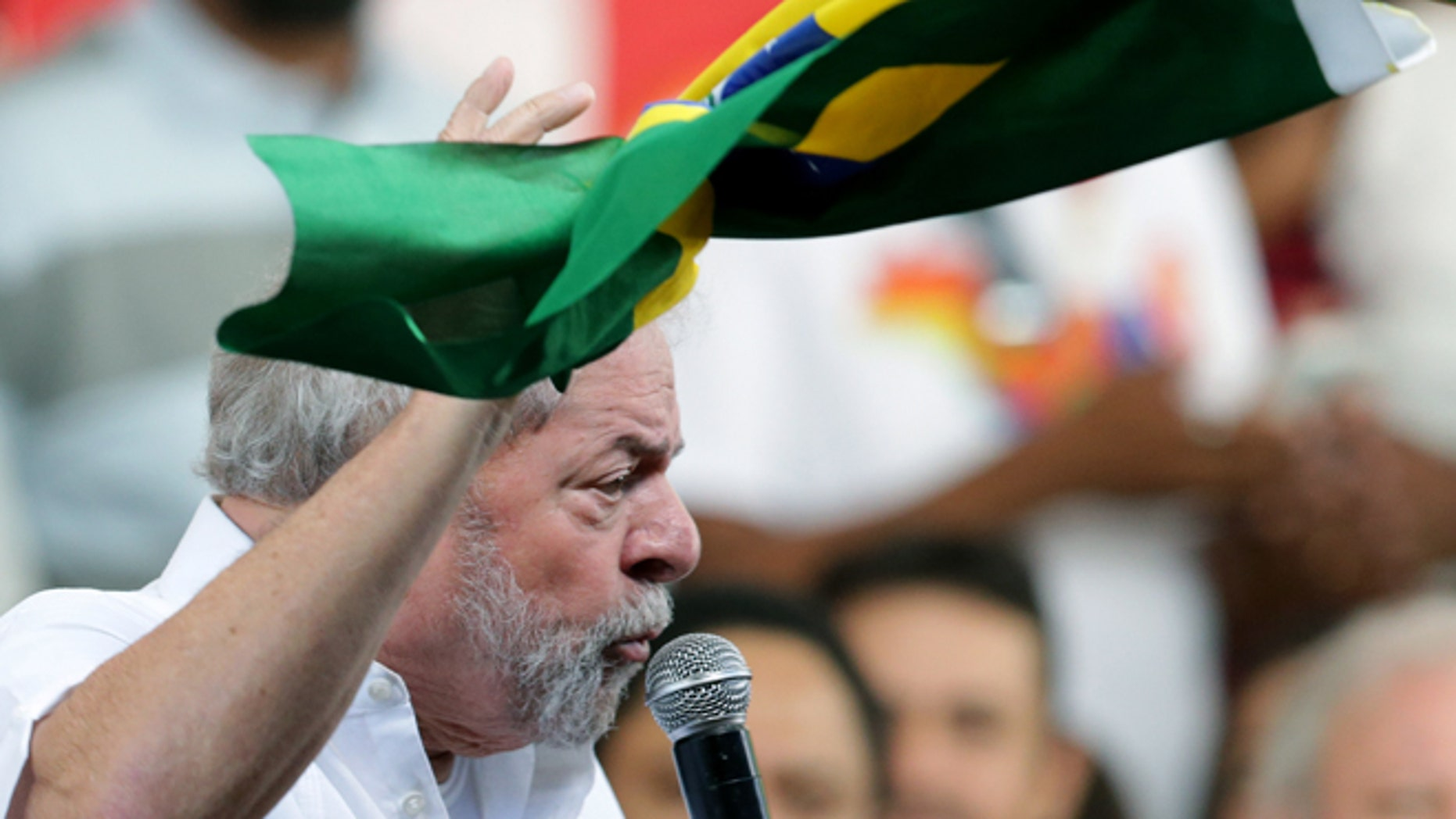 Brazil's former President Luiz Inacio Lula da Silva, holds a Brazilian flag, while speaking during a rally of Social Movements for Democracy, in a camp set up by supporters of President Dilma Rousseff in Brasilia, Brazil, Saturday, April 16, 2016. The lower chamber of Brazil's Congress on Friday began a debate on whether to impeach Rousseff, a question that underscores deep polarization in Latin America's largest country and most powerful economy. The crucial vote is slated for Sunday. (AP Photo/Eraldo Peres)