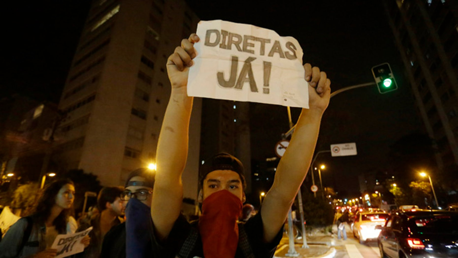 """A man holds a sign that reads """"Elections now"""" during a protest against President Michel Temer in Sao Paulo, Brazil, Sunday, Sept. 4, 2016. Temer was sworn in as Brazil's new leader on Wednesday following the ouster of President Dilma Rousseff. (AP Photo/Nelson Antoine)"""