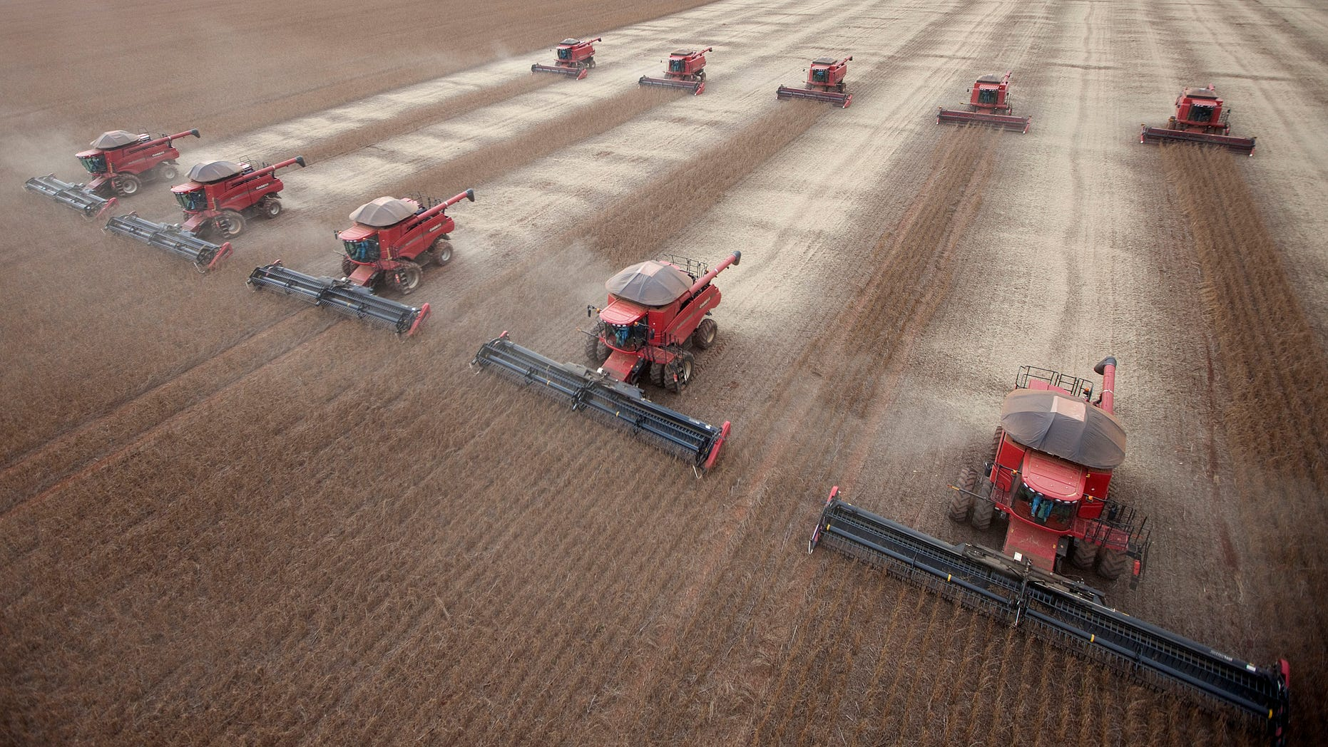 In this photo taken March 27, 2012, workers use combines to harvest soybeans in Tangara da Serra, State of Mato Grosso, Brazil. (AP Photo/Andre Penner)