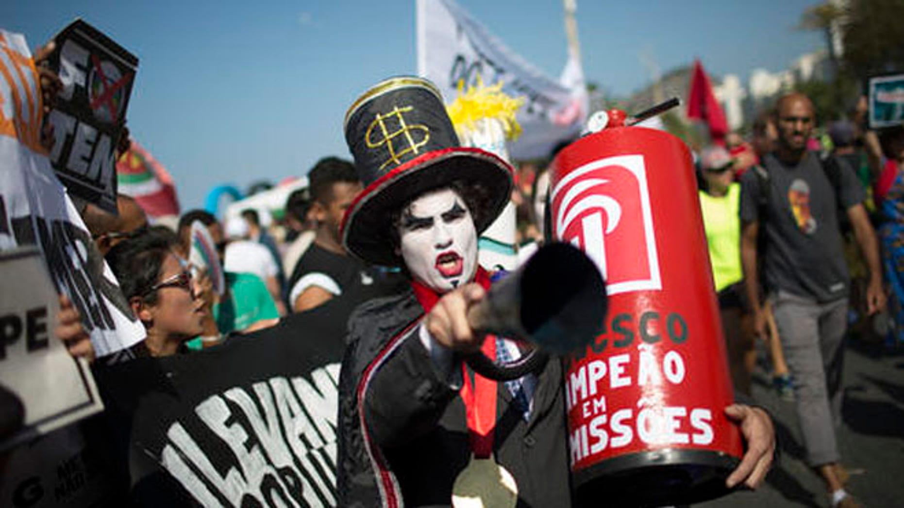 "A demonstrator in a costume depicting a banker and holding a replica of a fire extinguisher for putting out the ""flame"" of an imitation Olympic torch, takes part in a protest against the interim Brazilian president Michel Temer, and the Rio's 2016 Summer Olympics, on the route of the Olympic torch, at the Copacabana beach, in Rio de Janeiro, Brazil, Friday, Aug. 5, 2016. (AP Photo/Leo Correa)"