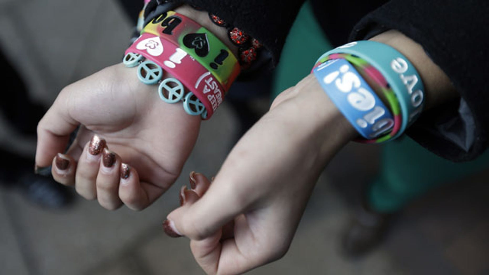 """FILE - In this Feb. 20, 2013 file photo, Easton Area School District students Brianna Hawk, 15, left, and Kayla Martinez, 14, display their """"I (heart) Boobies!"""" bracelets for photographers outside the U.S. Courthouse in Philadelphia. (AP Photo)"""